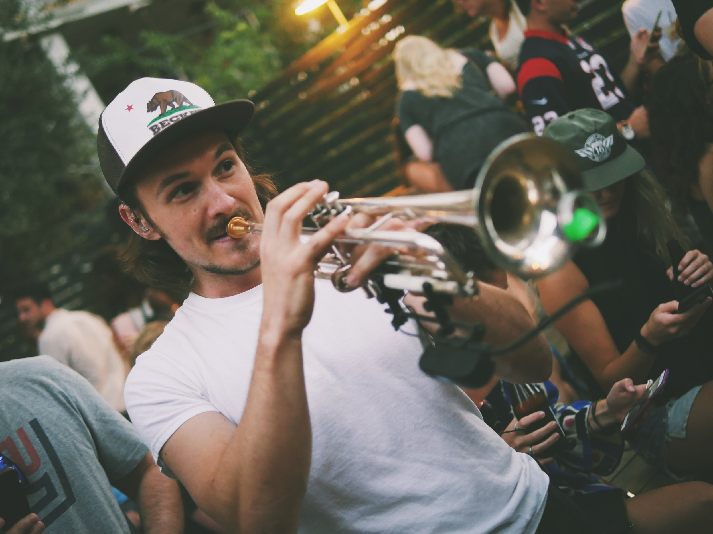 A man in a hat playing a trumpet in a crowd of people outdoors