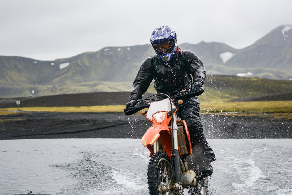 person riding dirt motorcycle on body of water during daytime