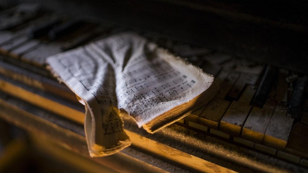 torn music sheet on piano keys