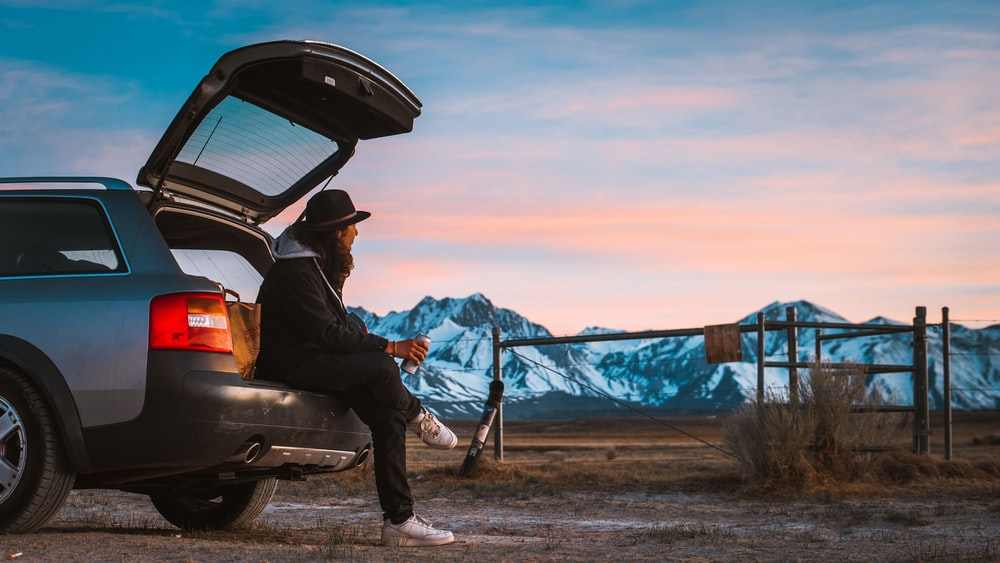 man sitting on car's tail looking at ranch