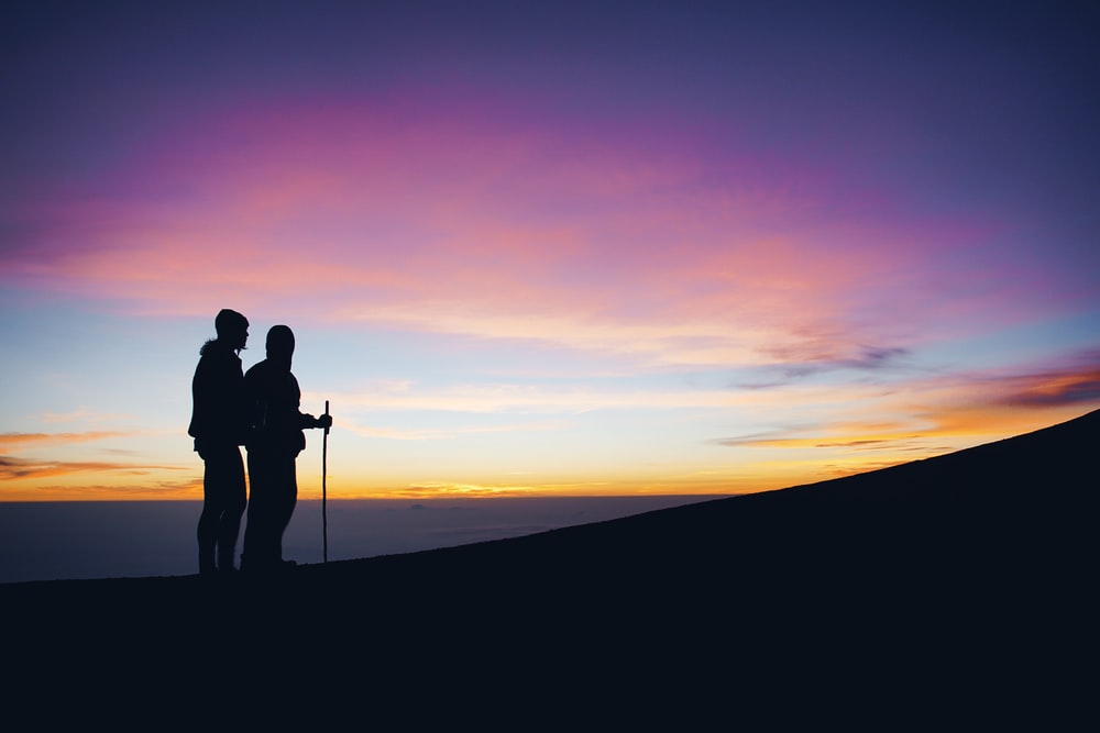 silhouette of two man walking on top of mountain