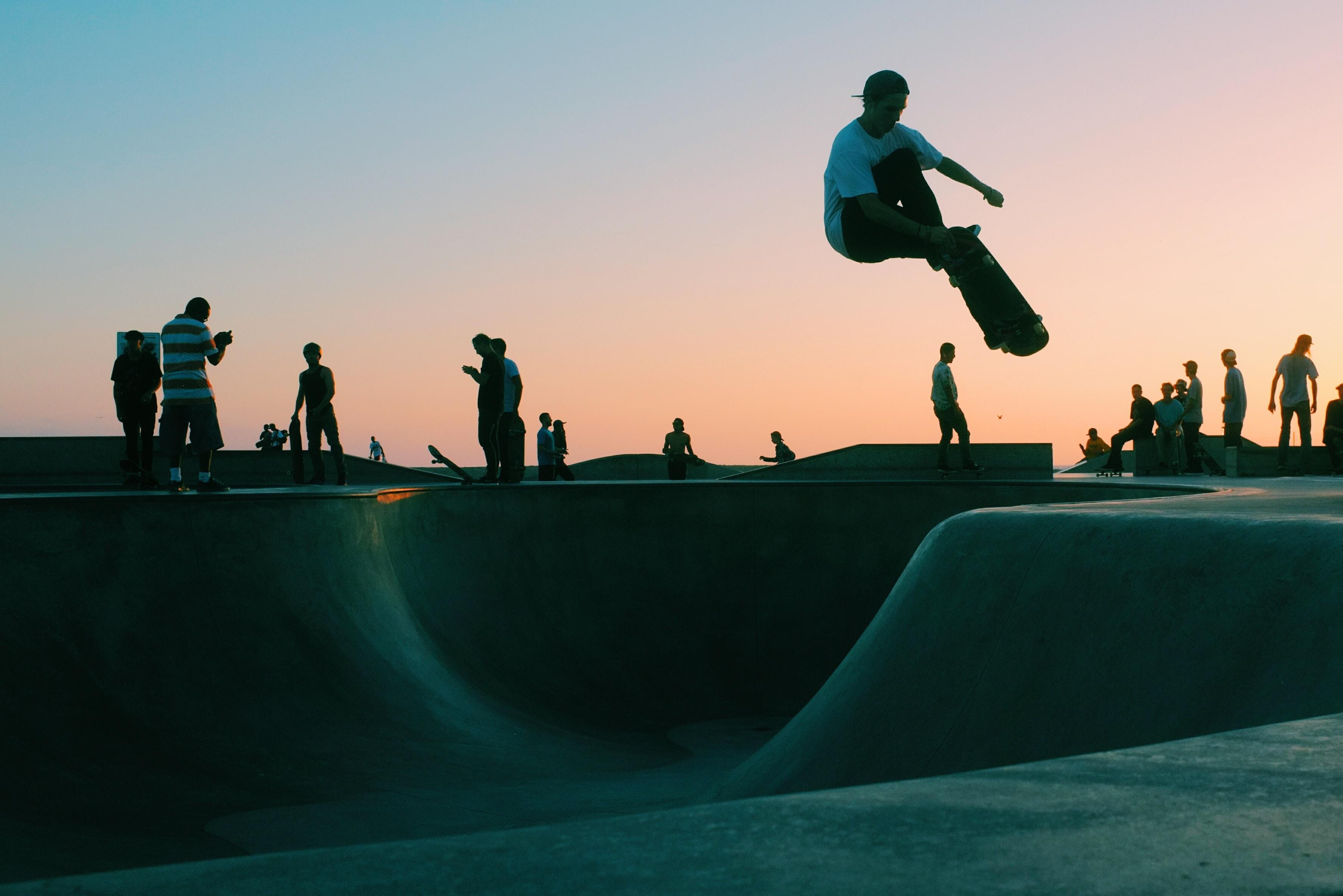 man doing trick at skateboard park during sunset