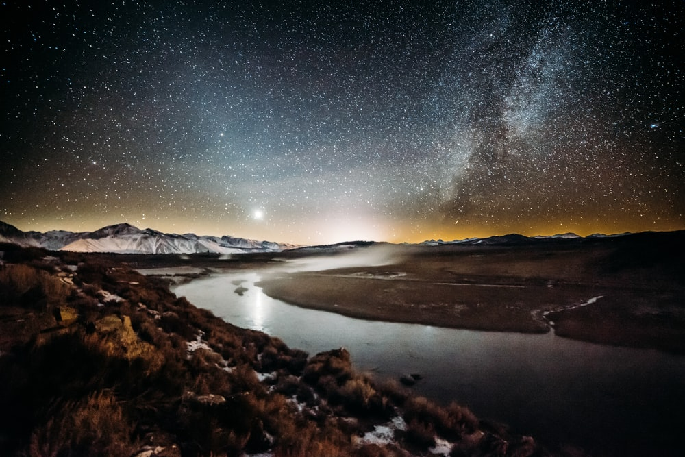 river surrounded by brown grass field under star sky