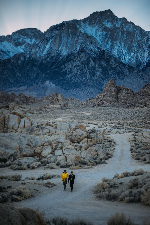 two men walking on pathway near mountain