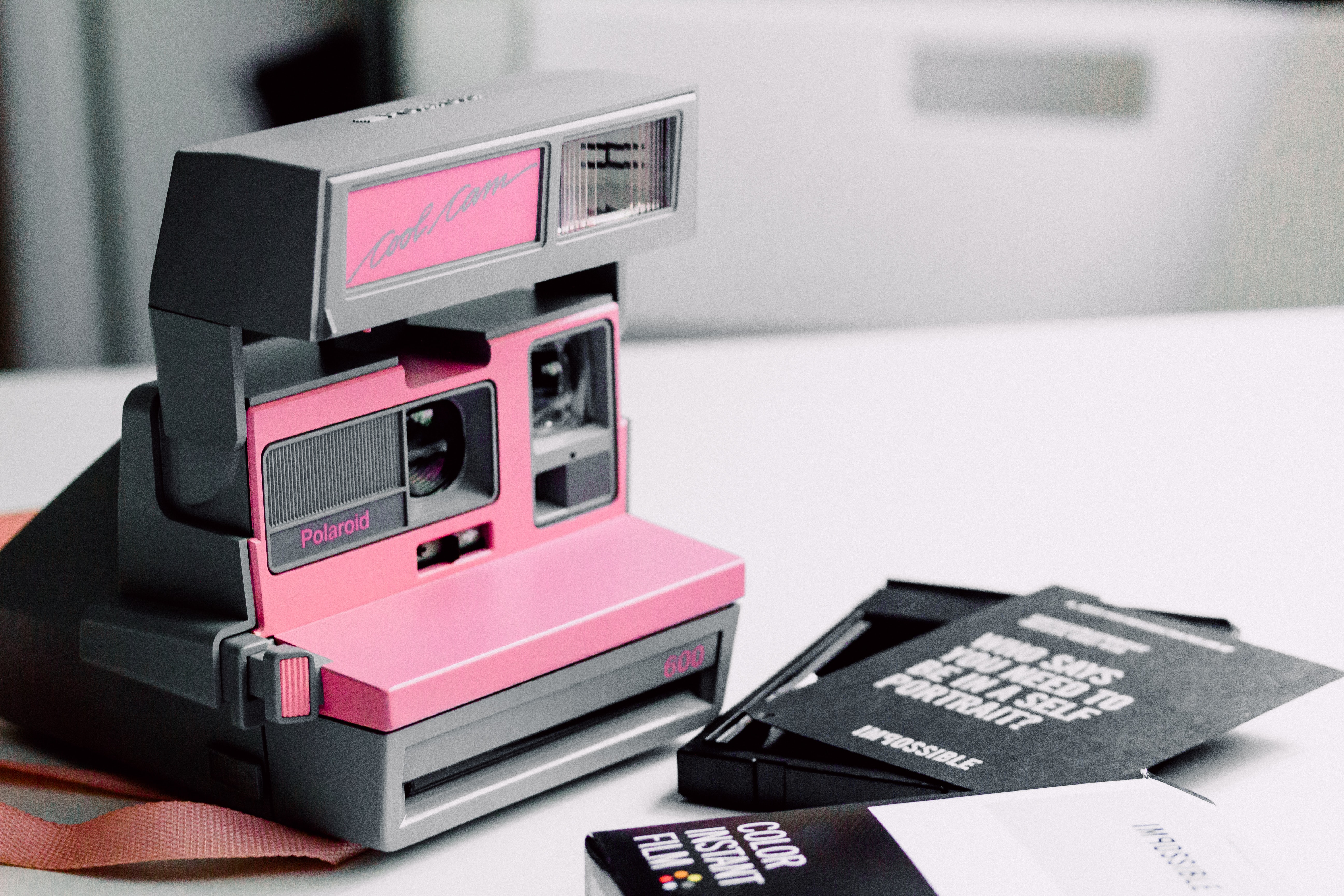 A pink Polaroid camera on a white surface