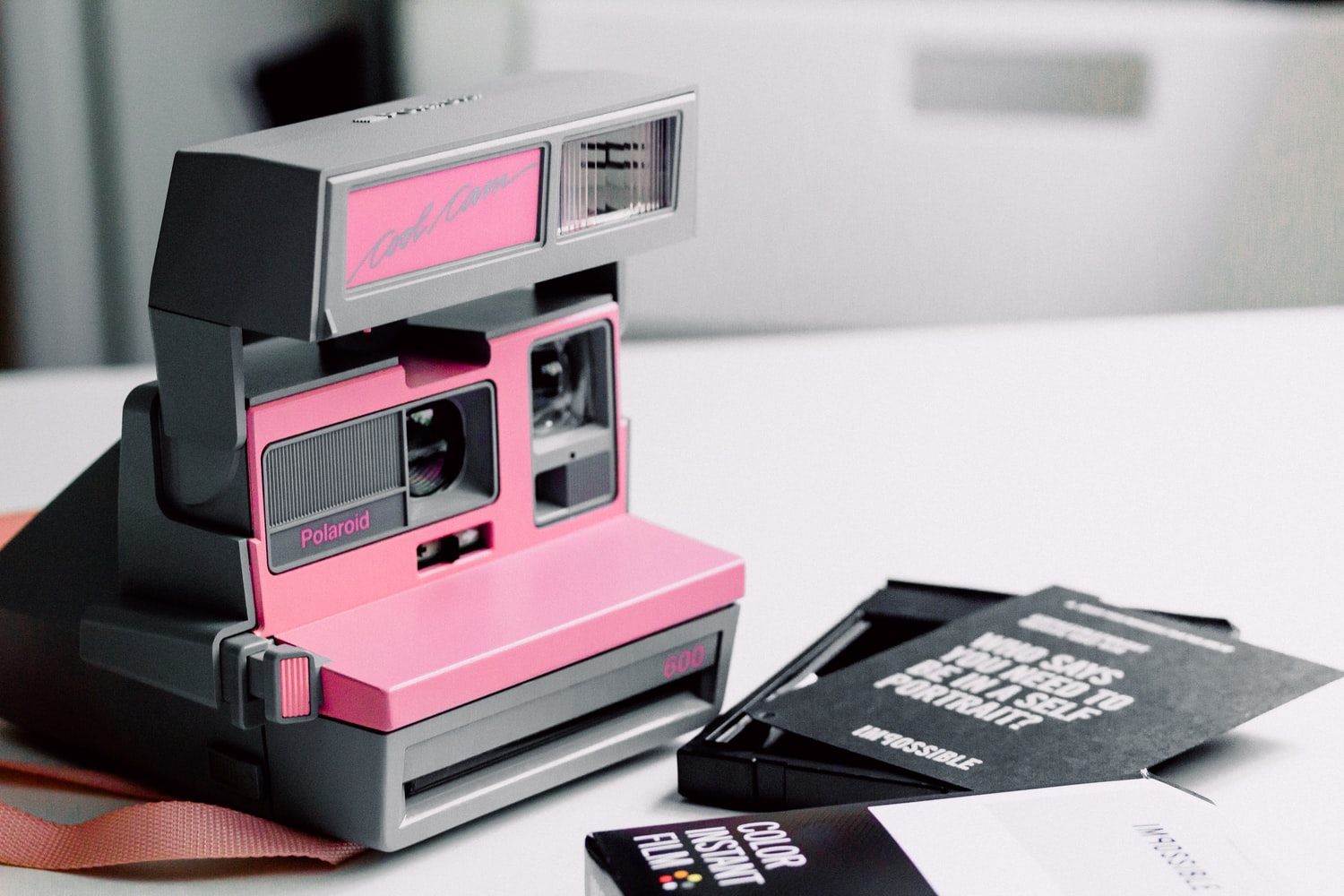 Pink polaroid camera on the table