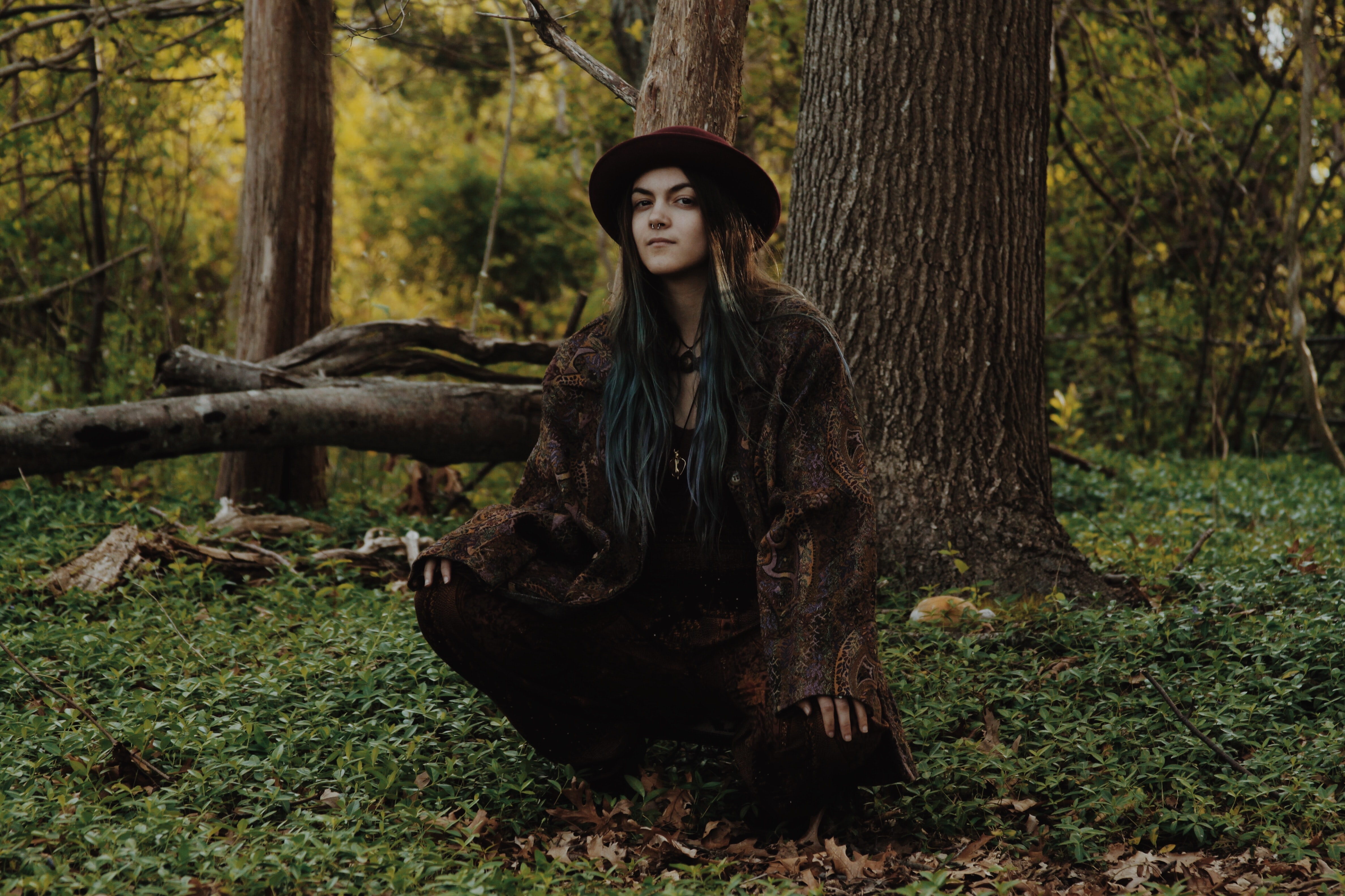 A young bohemian woman crouching under a tree in a forest