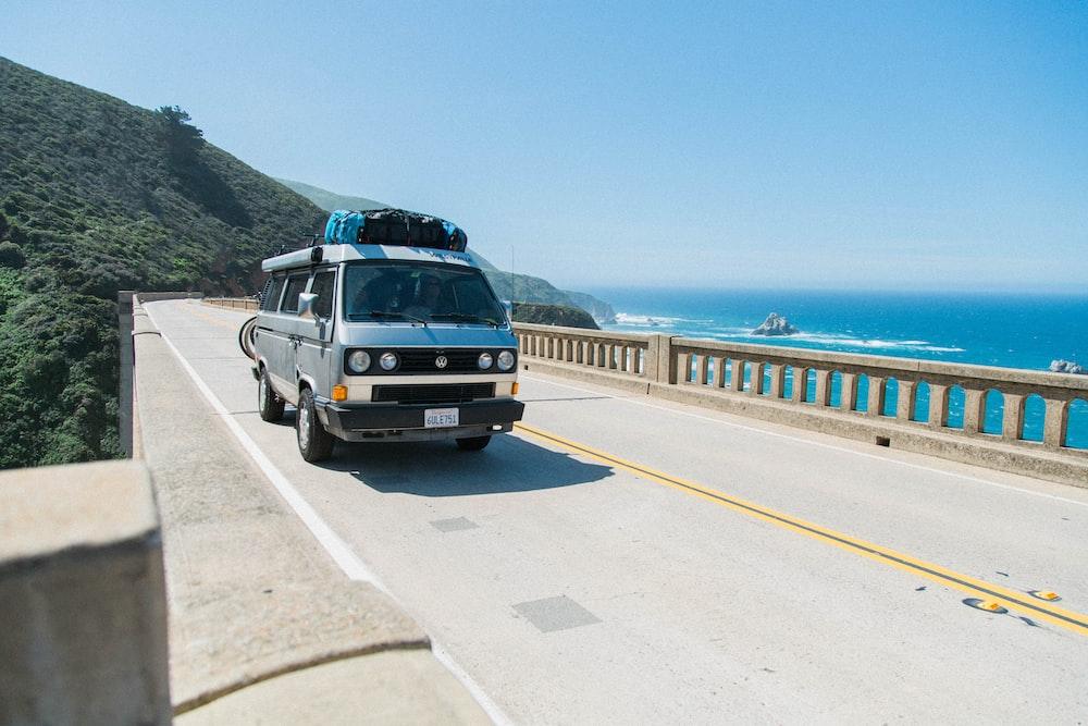 van crossing bridge over body of water