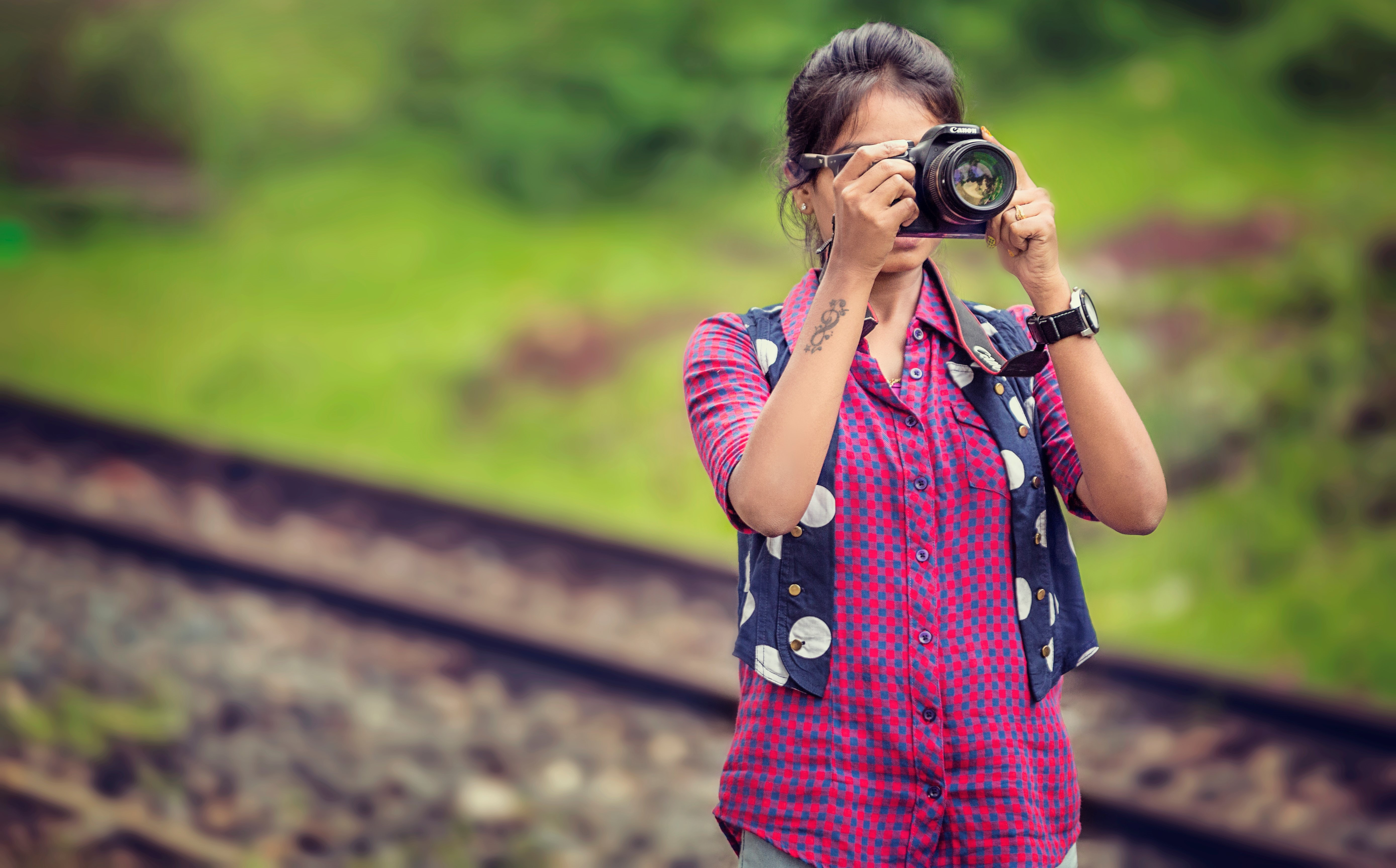 Woman wearing pink shirt, blue vest and watch while taking pictures with a camera