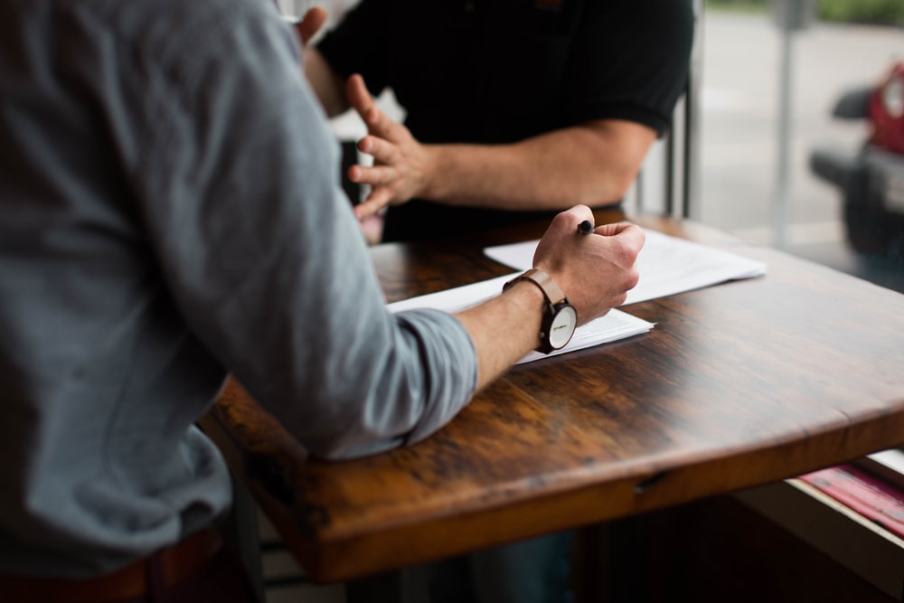 Two people discussing business over a table with documents