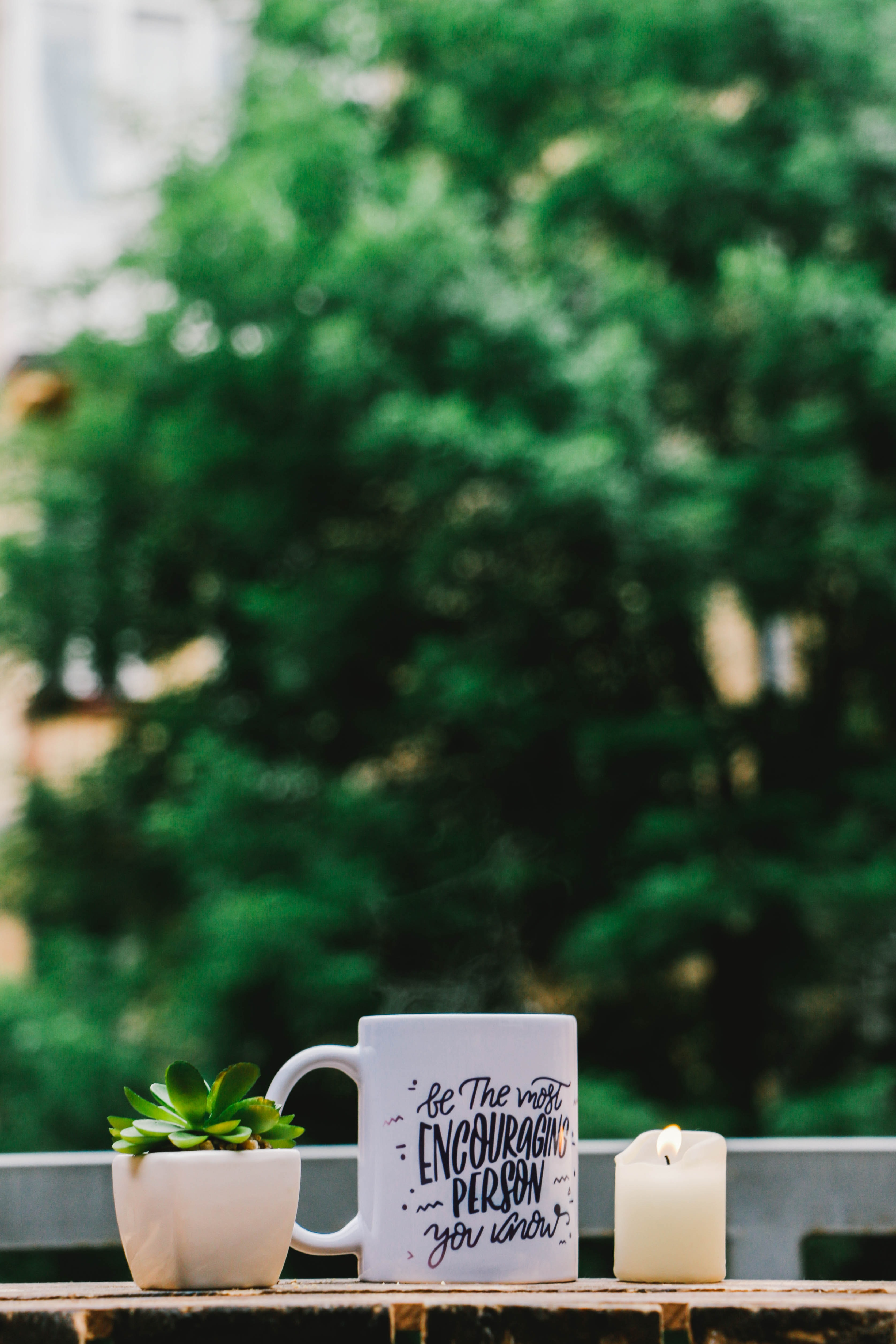 """A white mug with """"be the most encouraging person you know"""" written on it next to a potted plant and a candle"""