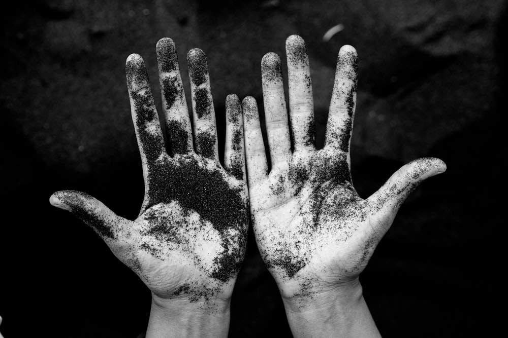 A black and white photograph showing some black sand on a pair of open hands
