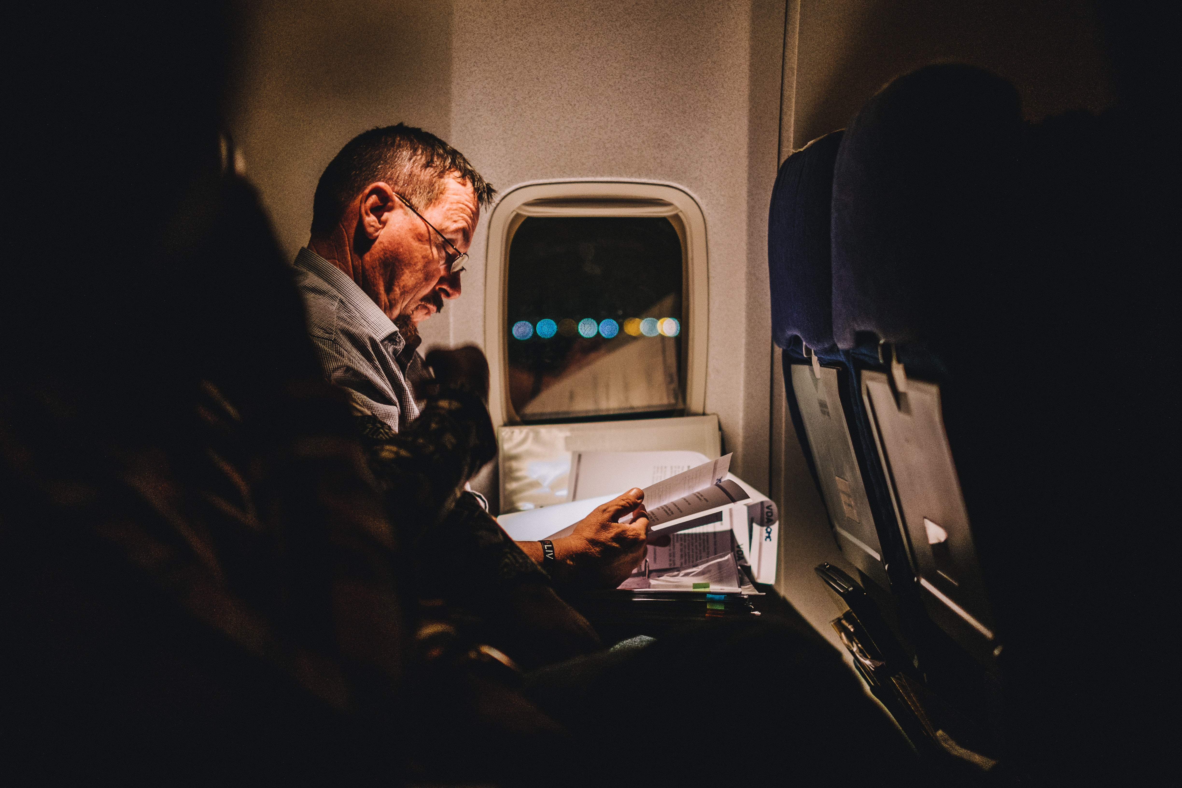 A man looks at documents in a plane with the bokeh effect in the window.