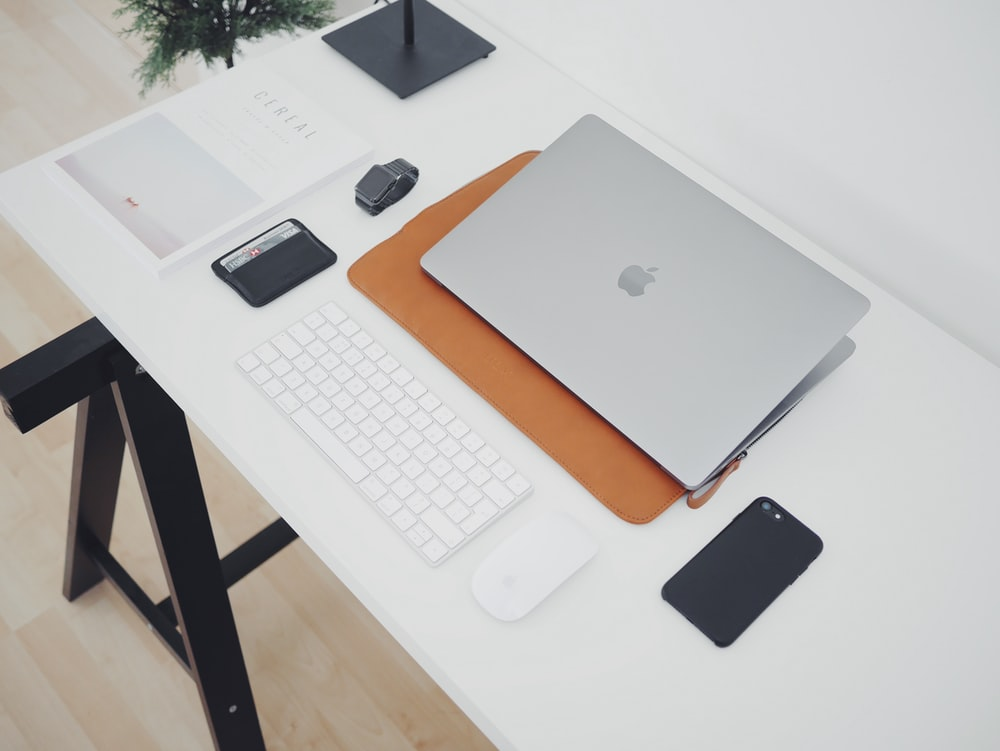 silver MacBook and phone on white table