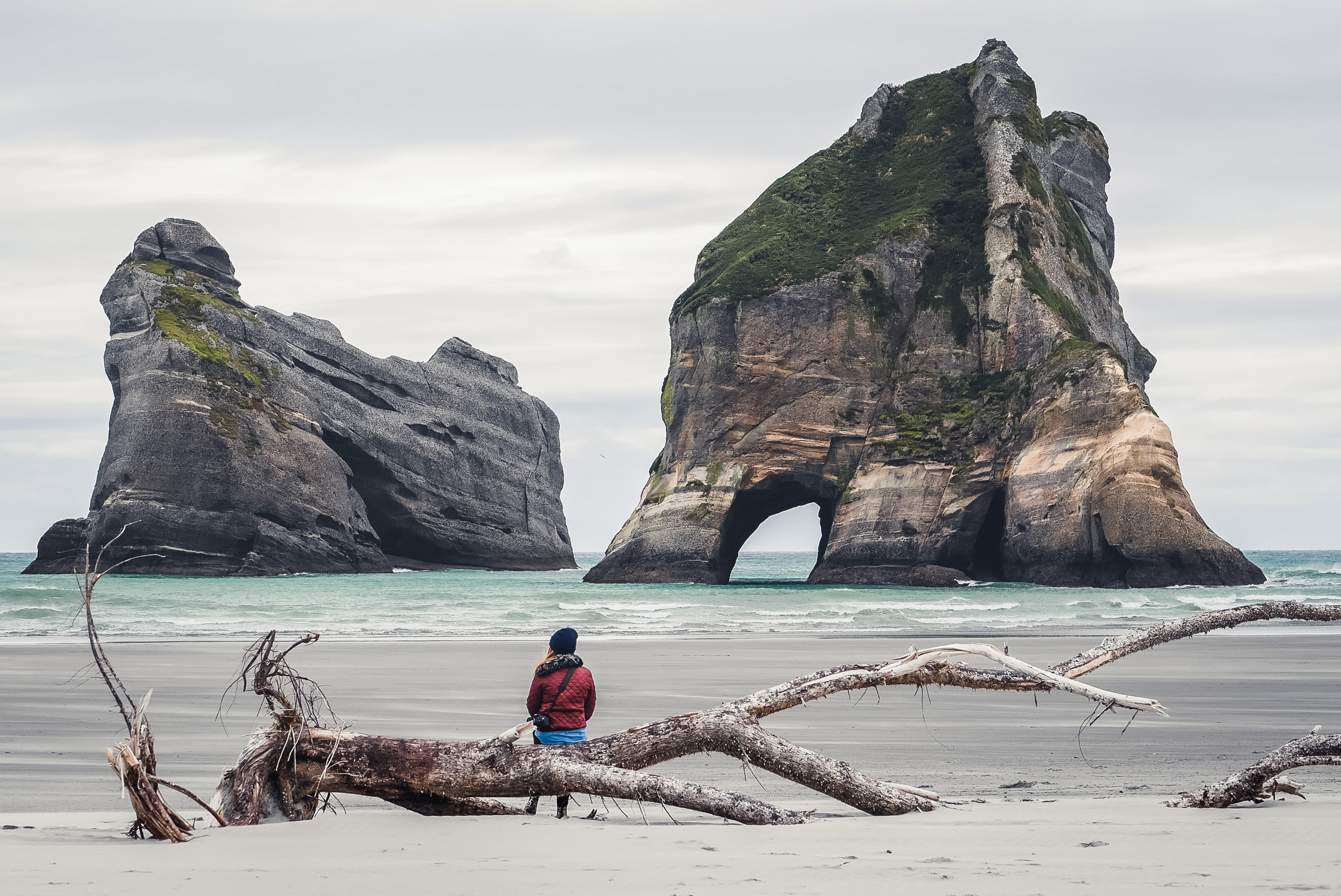 Rock formations in front of a woman sitting on a dead tree at the Wharariki Beach