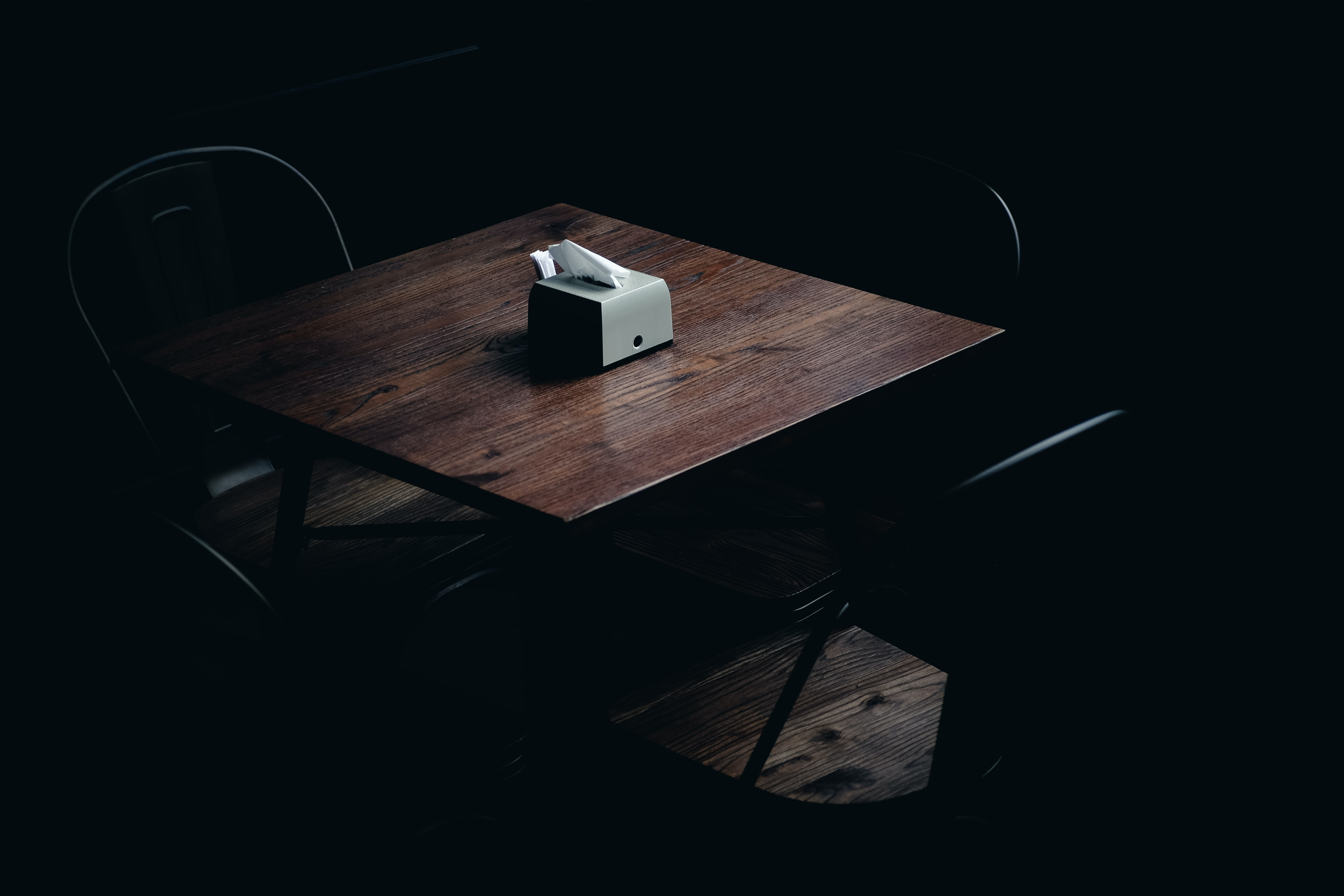 Dark wooden table and chairs in a dark room with napkin box on table