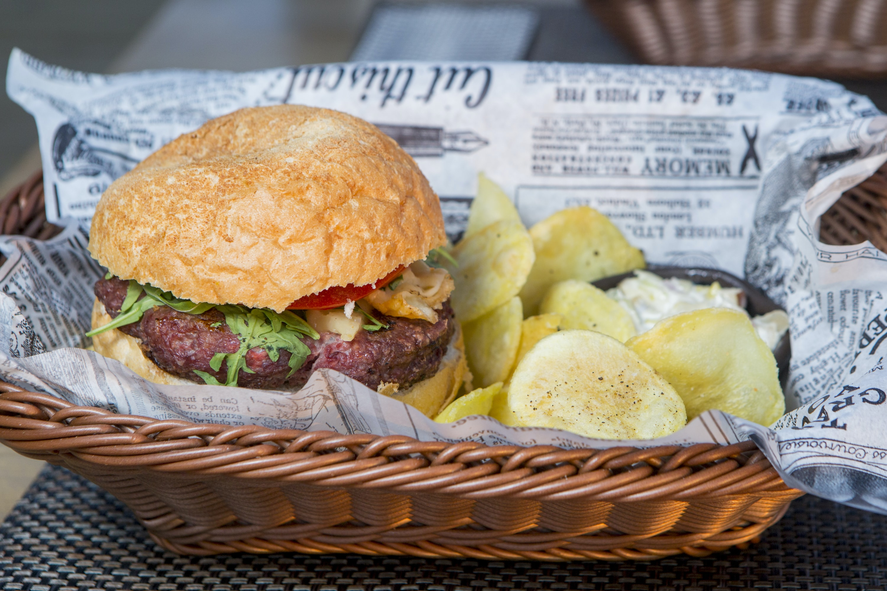 Hamburger and potato chips in a basket with newspaper lining