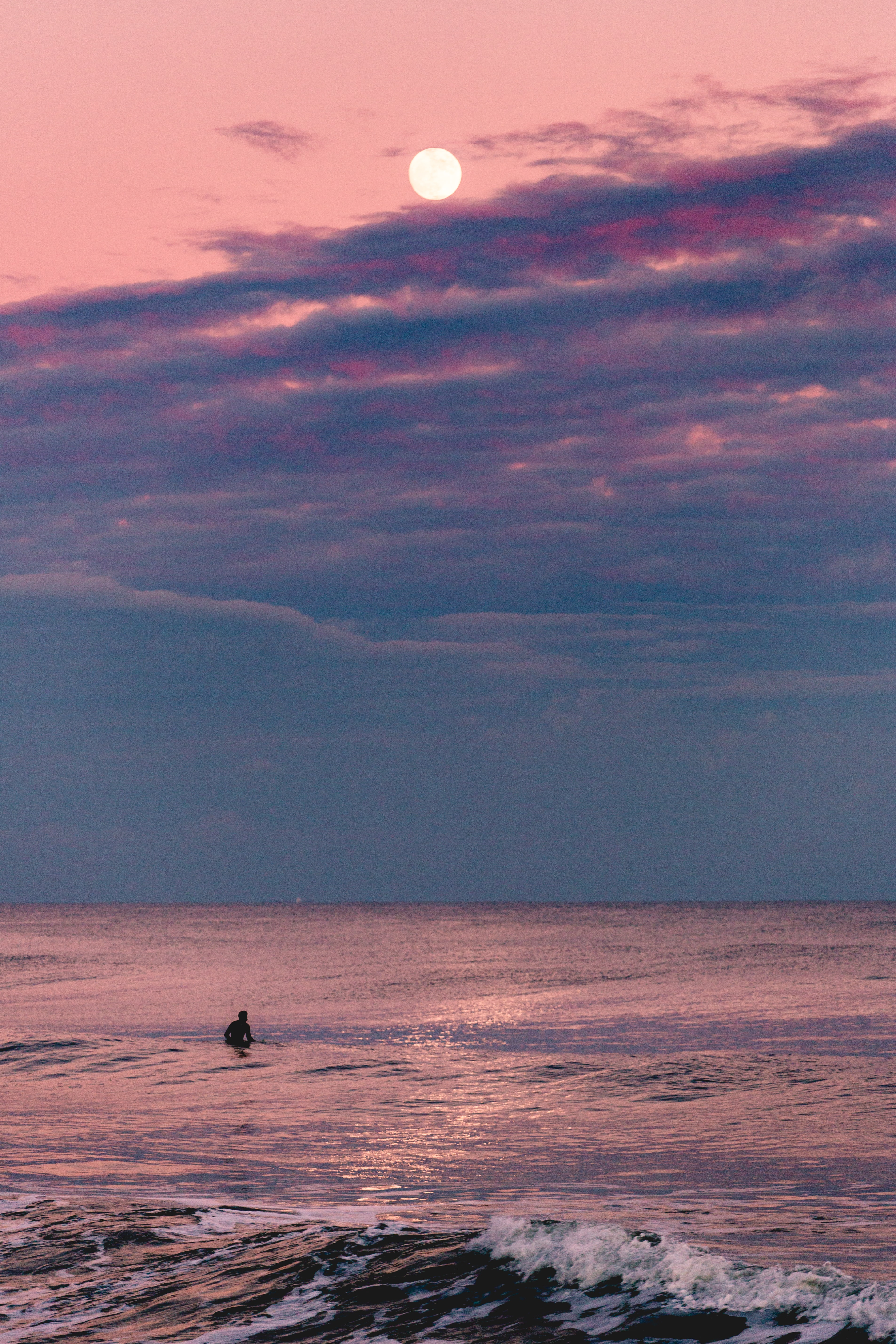 A surfer at Avon-by-the-sea at dusk with a full moon above on a pink cloudy sky