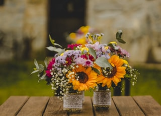two bouquet of petaled flowers on brown wooden table