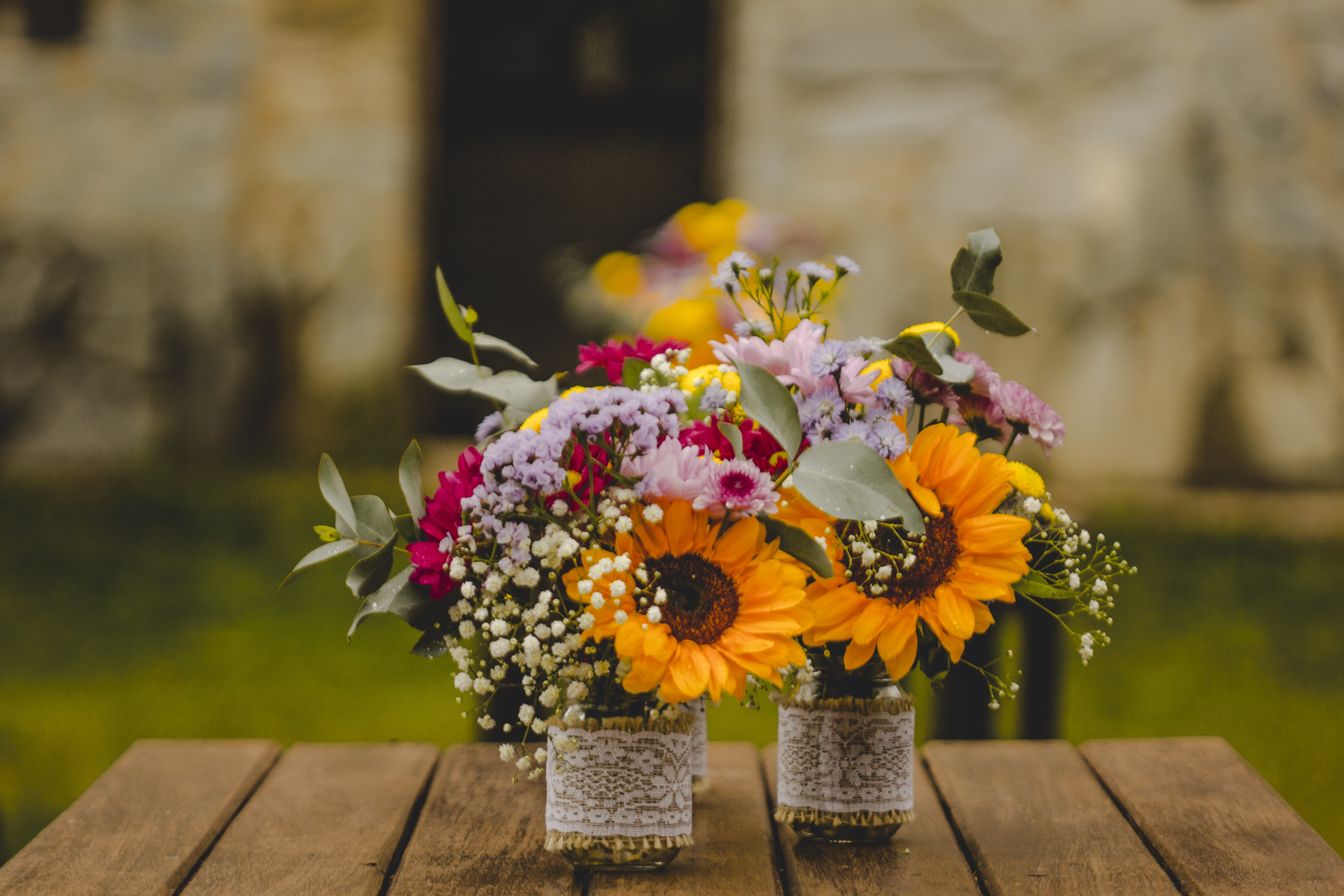 Two vases with collections of diverse flowers on a wooden table outdoors