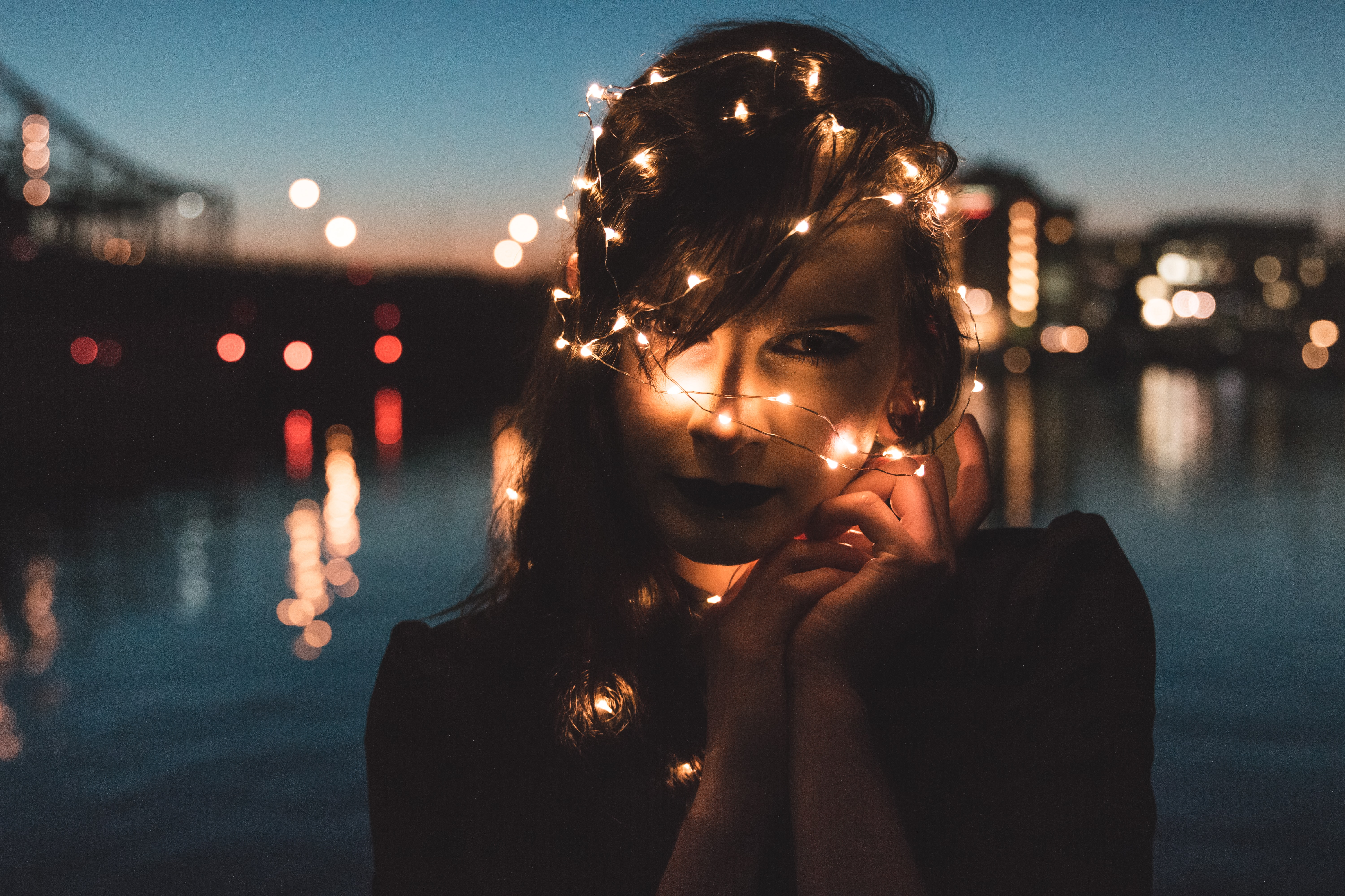 A woman with fairy lights wrapped around her head and the bokeh effect they are making in Boston