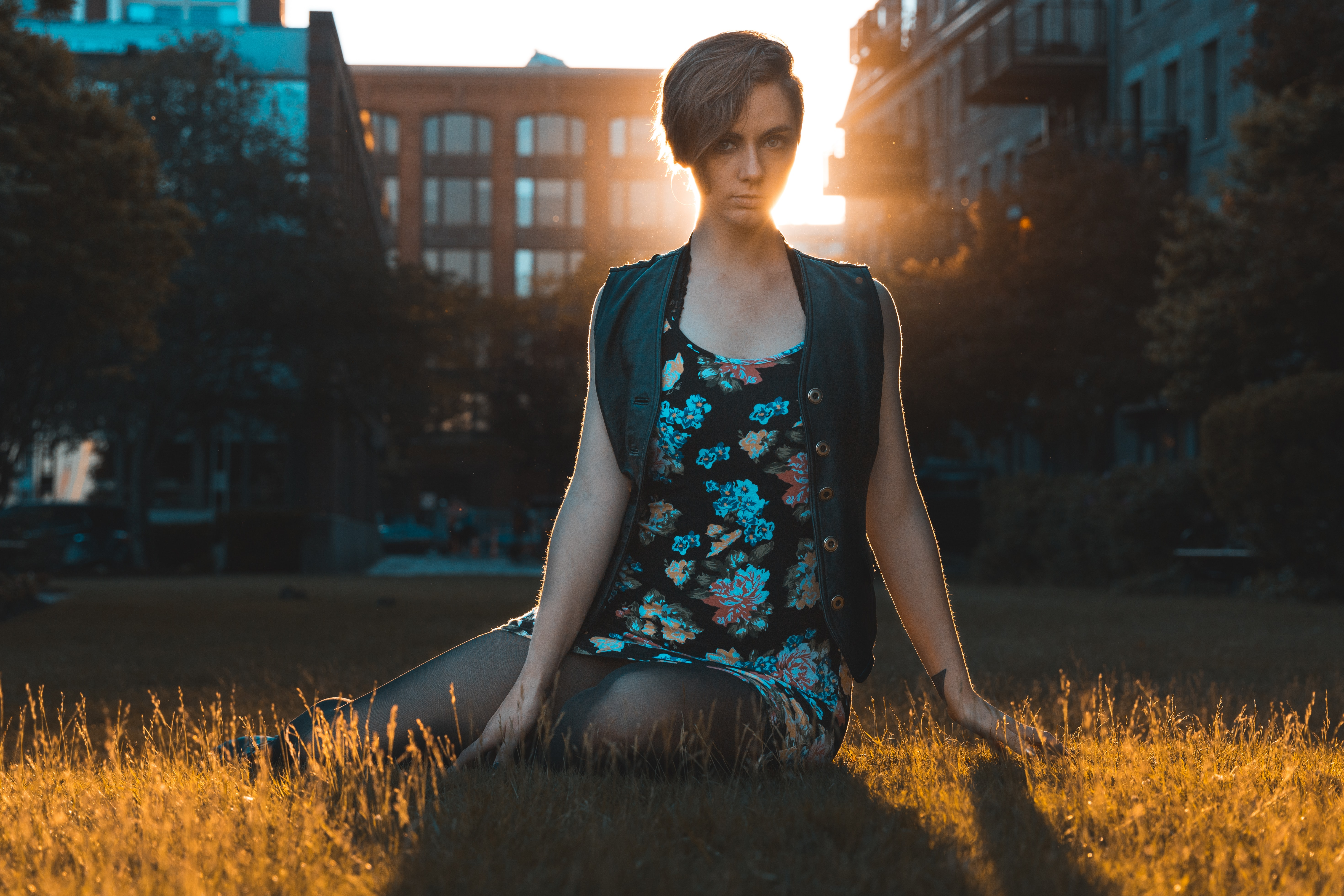 Backlit person in a floral dress siting in the grass staring seriously
