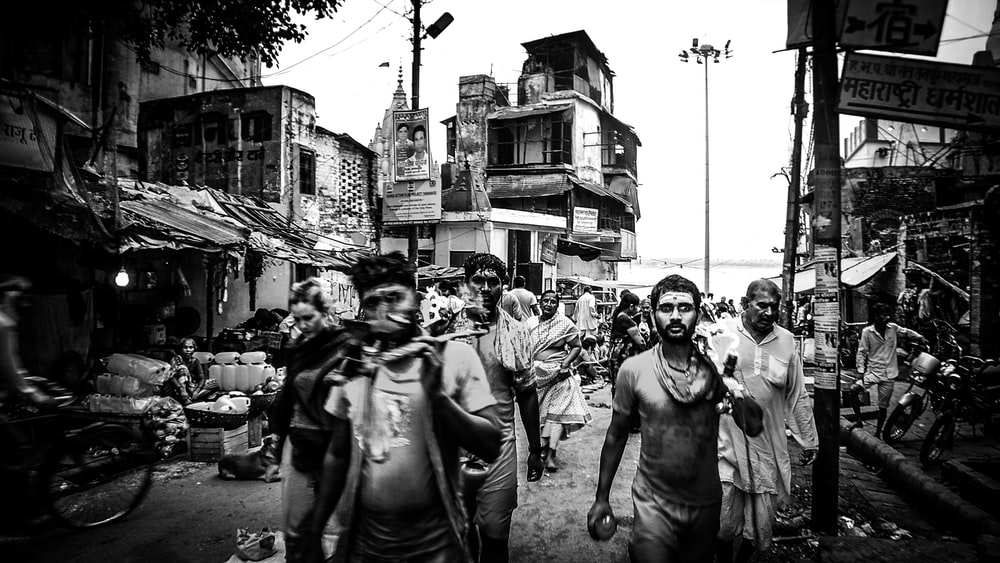 Black And White Shot Of Men Walking In Poor Community Varanasi
