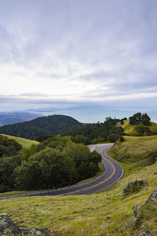 curve asphalt road on hill near sea under cloudy sky