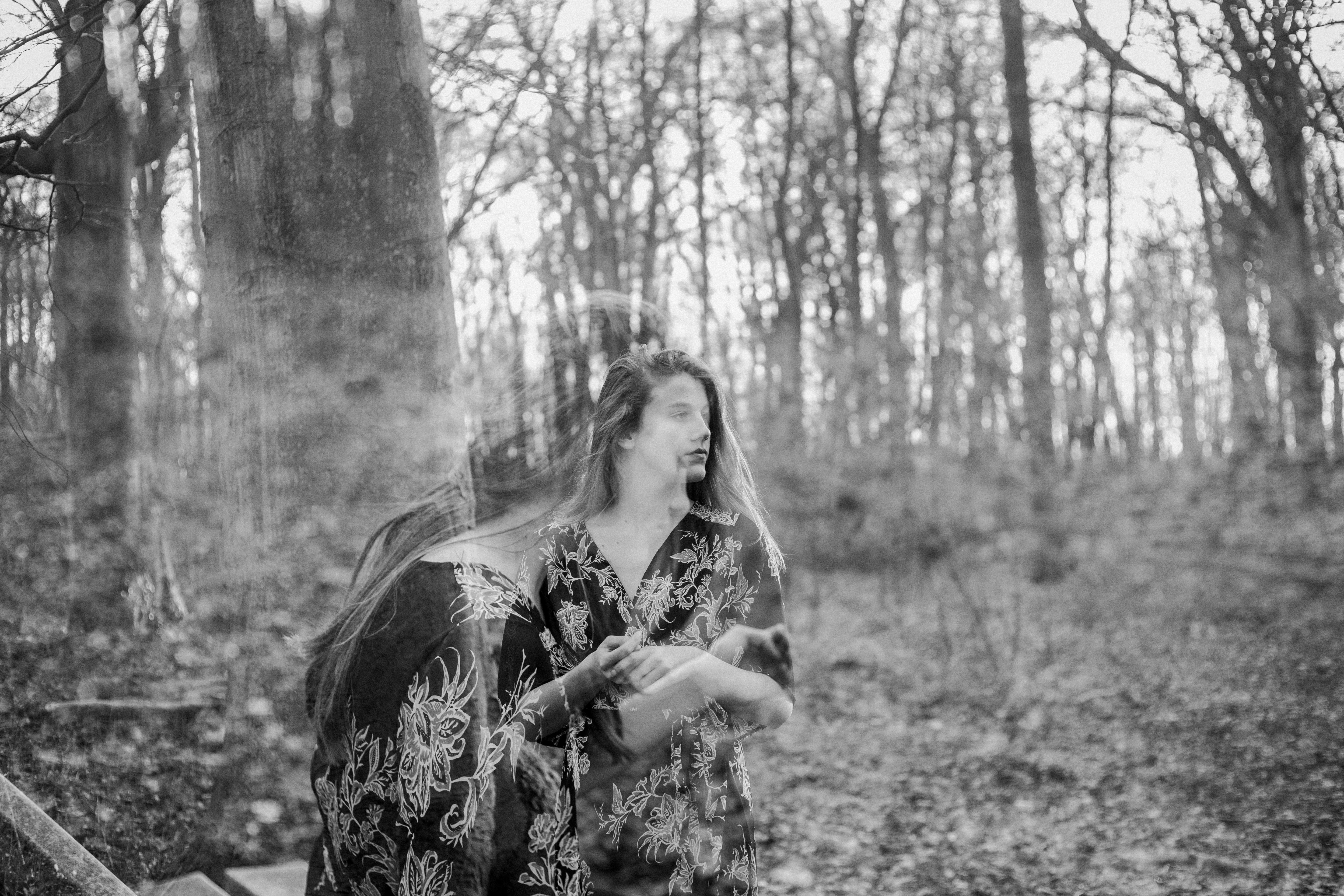 A black-and-white double exposure shot of a young woman in a forest