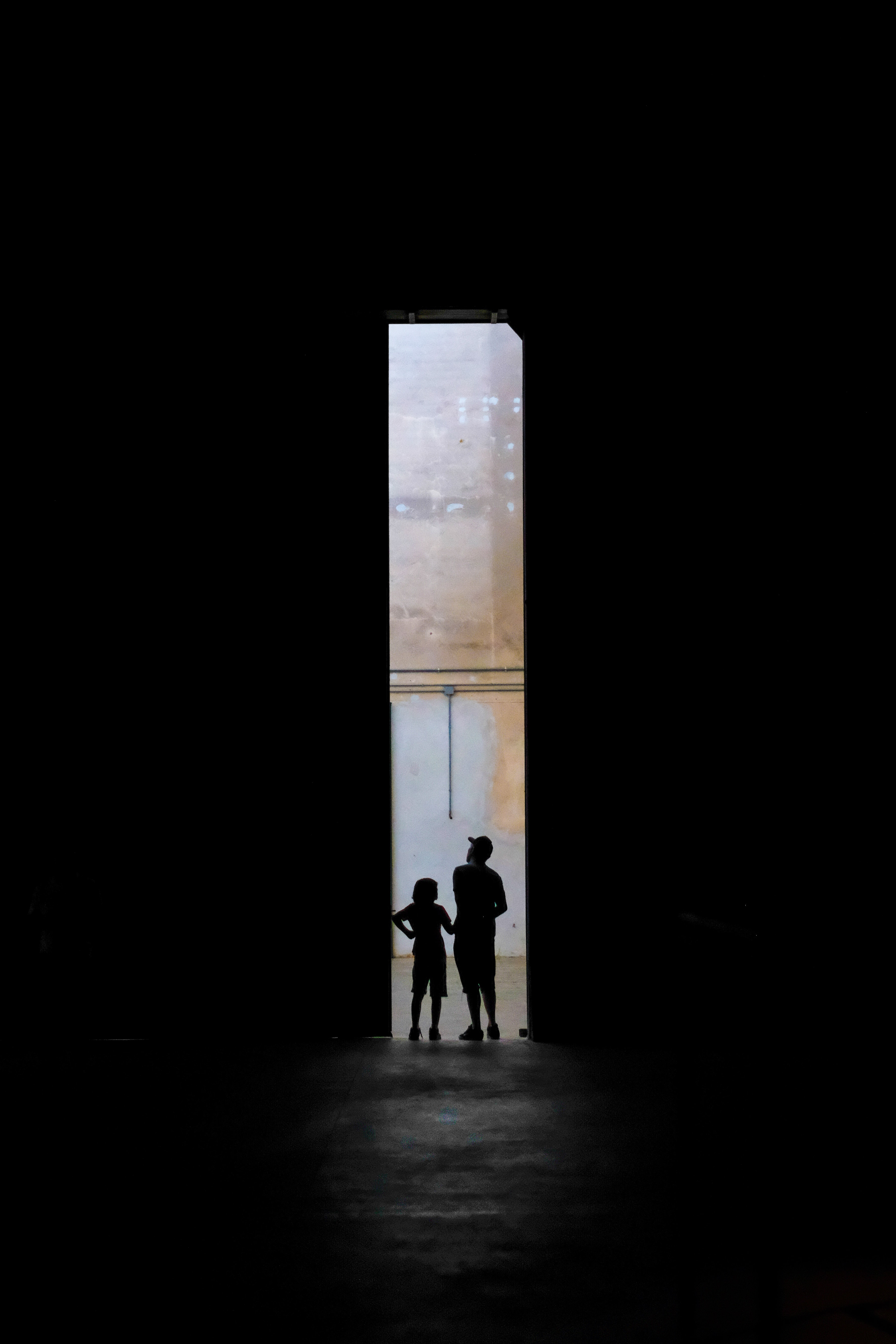 silhouette of two persons standing between doors