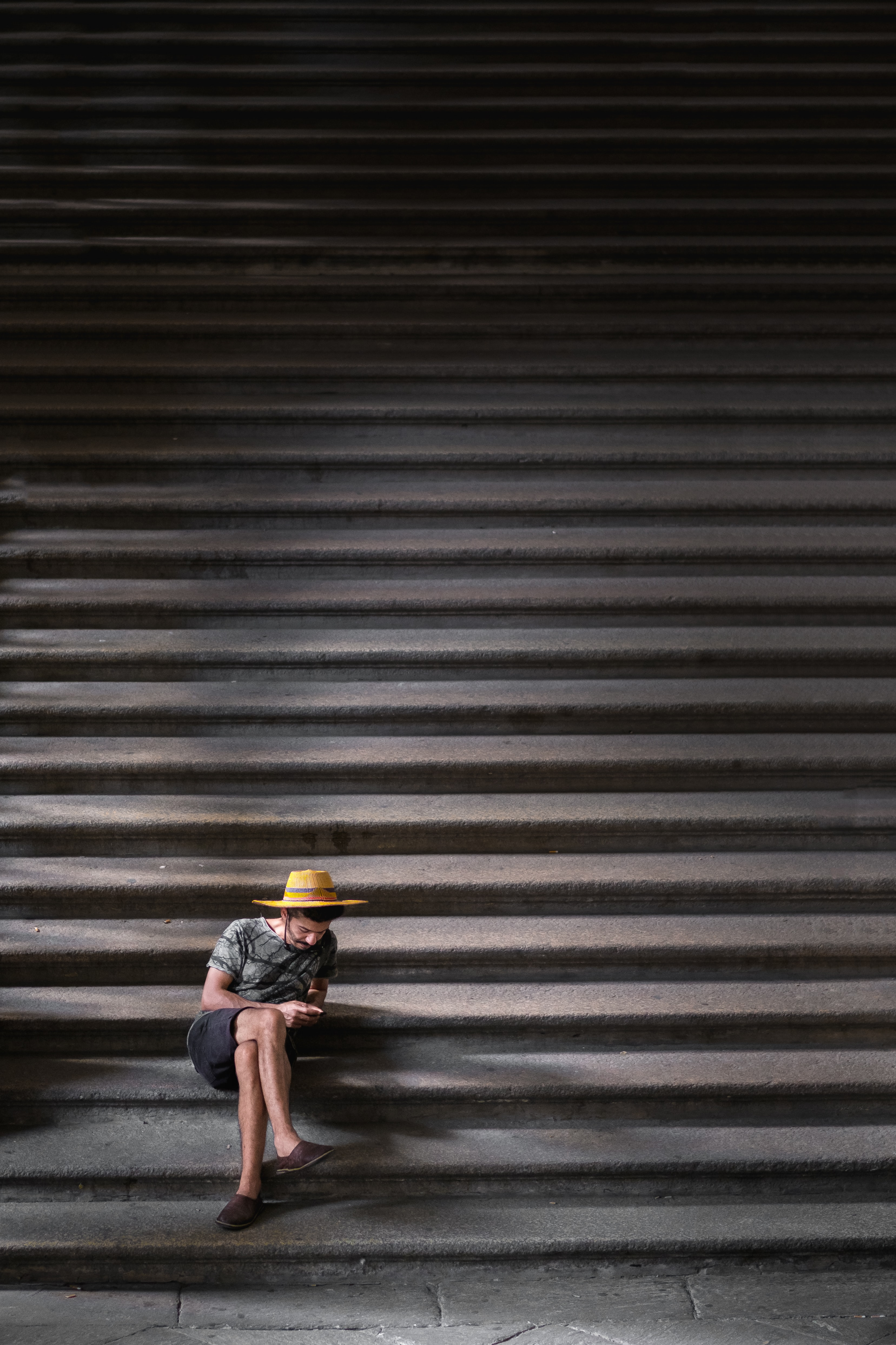 man crossing his legs sitting on staircase