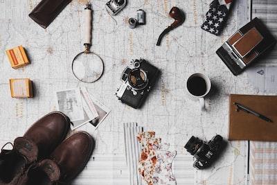 camera, pair of brown shoes, white ceramic mug, grey and black pen, brown smoking pipe