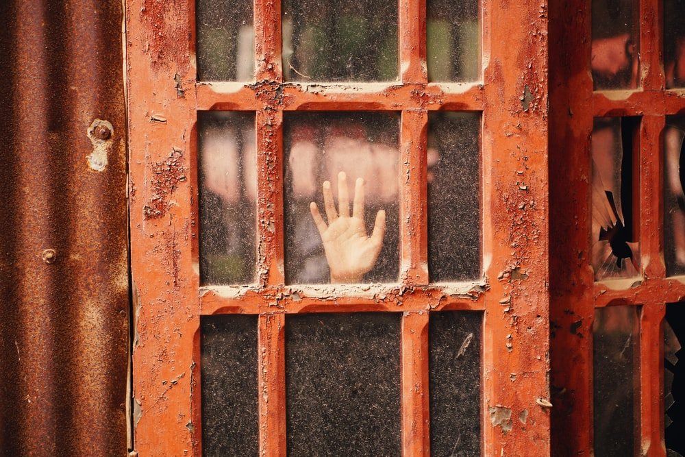 person hand on glass panel door with red wooden frame