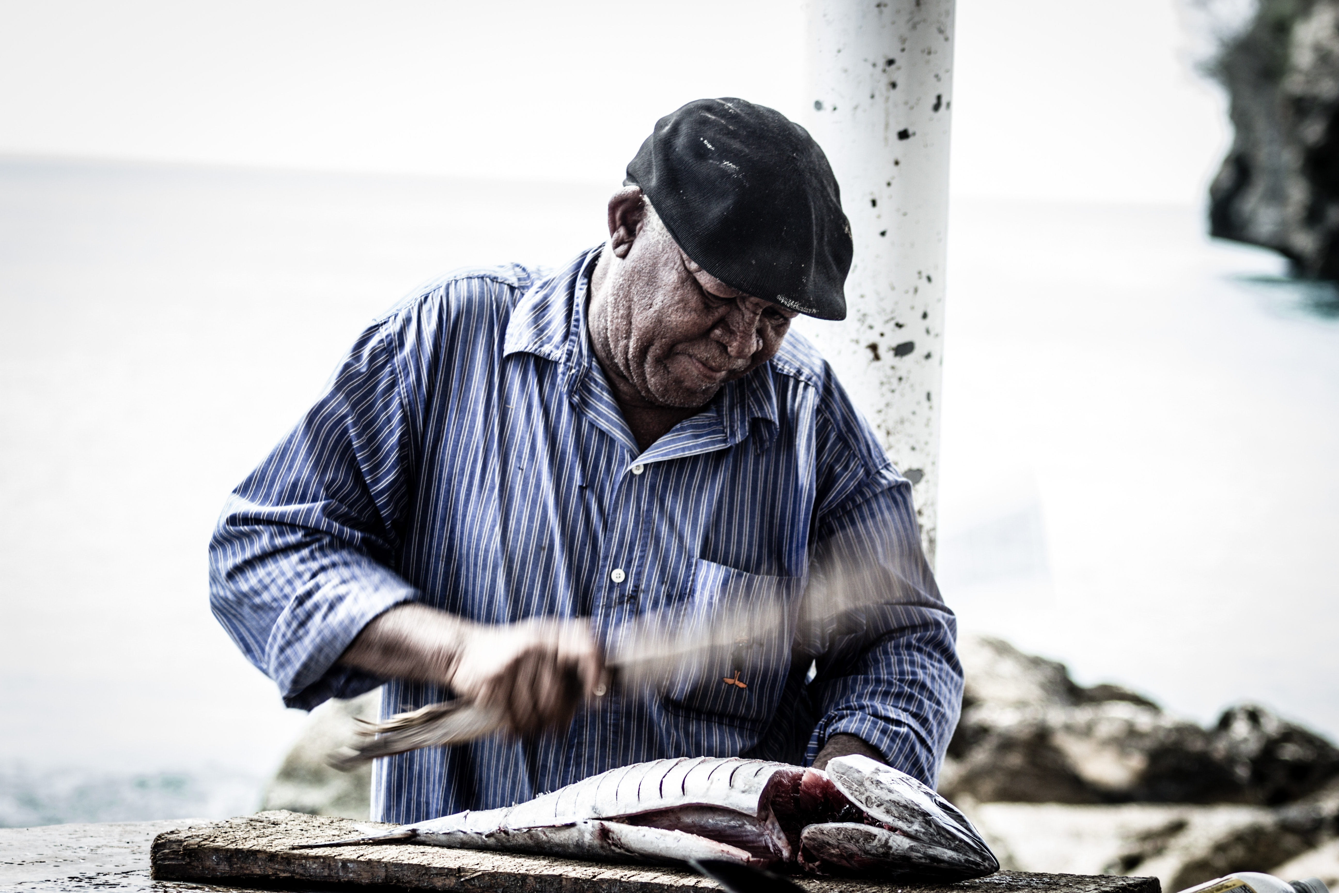 man cutting raw fish using knife