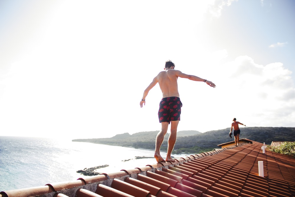 man walking on house roof