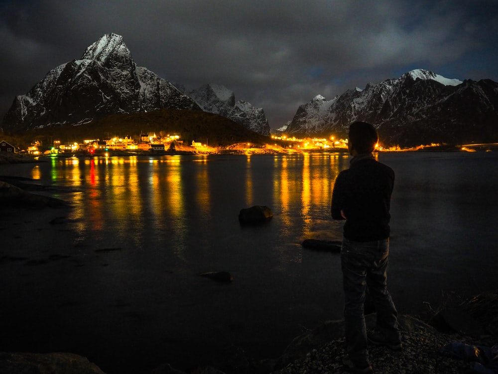 man standing near body of water far away from building during nighttime