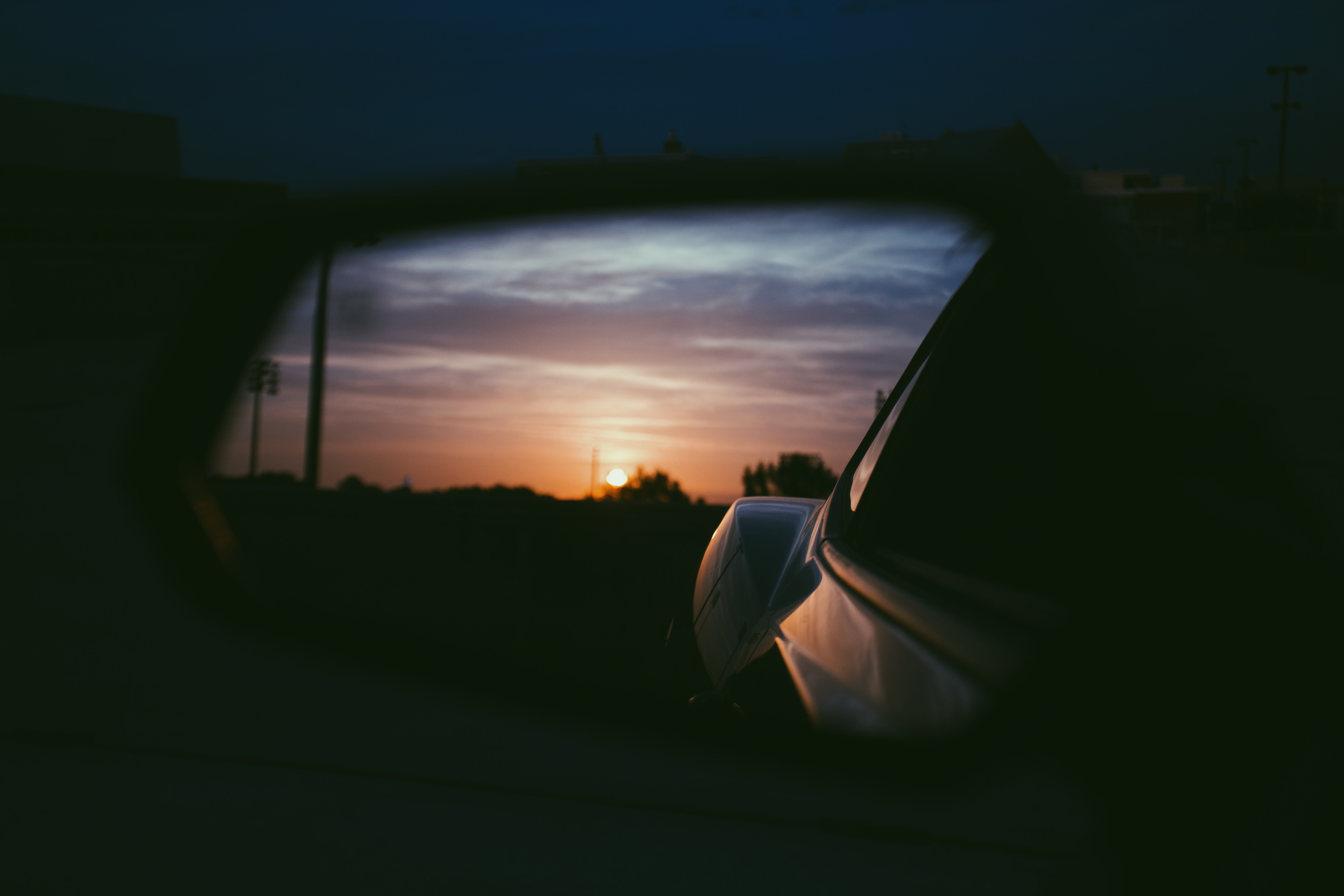 View of the sunset from the car on the side mirror
