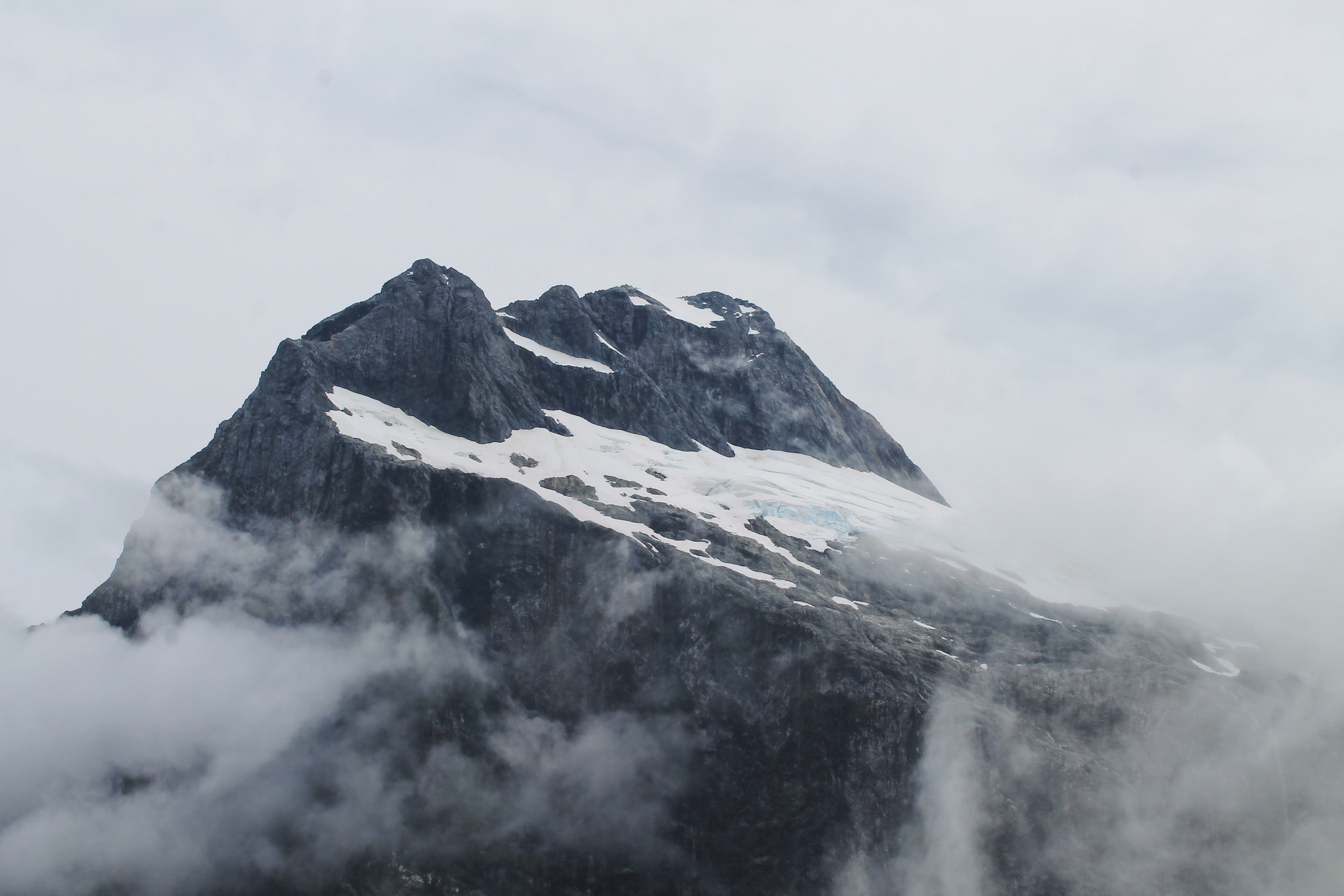 The peak of a mountain covered in snow and surrounded by fog