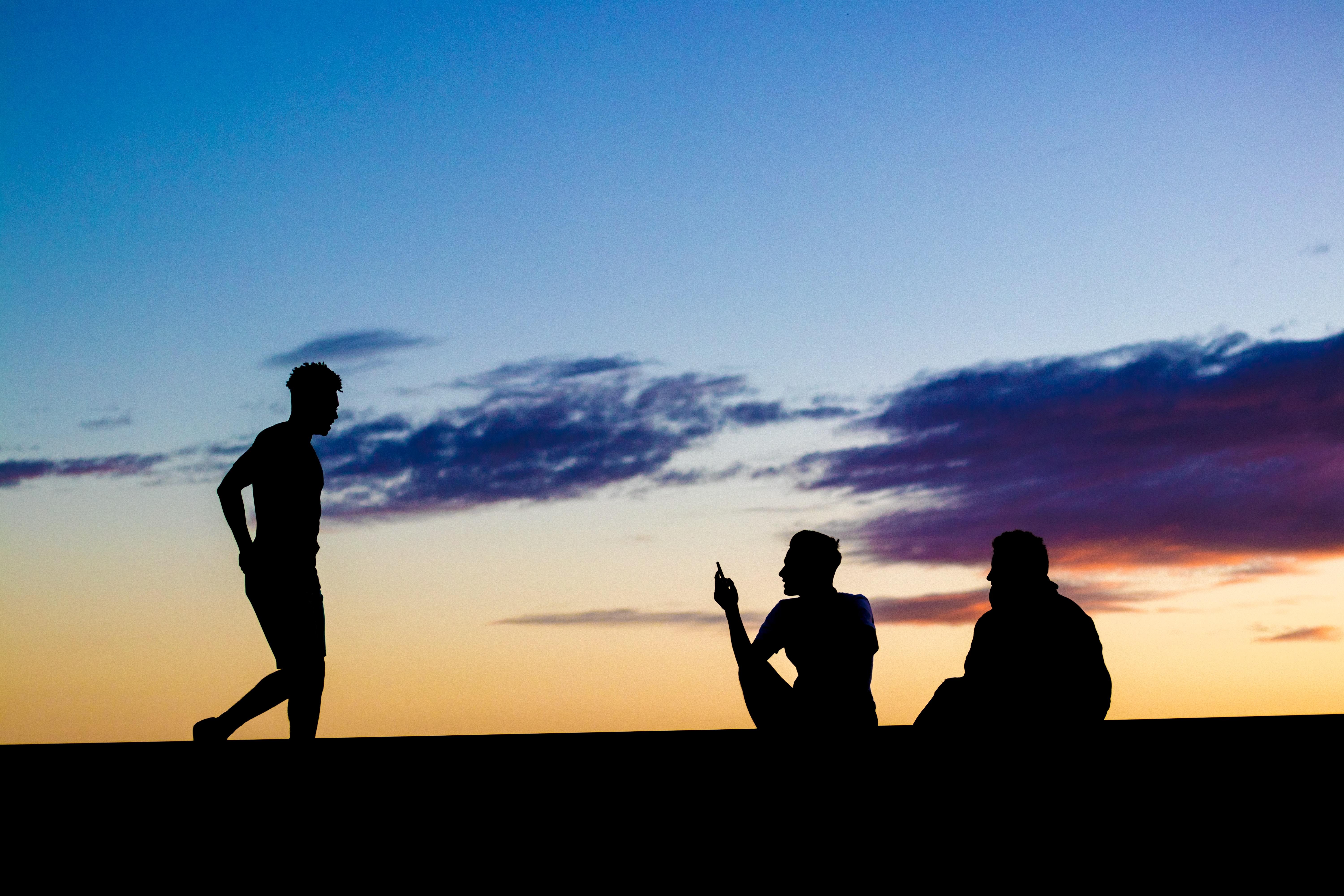 Silhouette of a man walking towards two friends sitting under a blue and orange Laton sunset