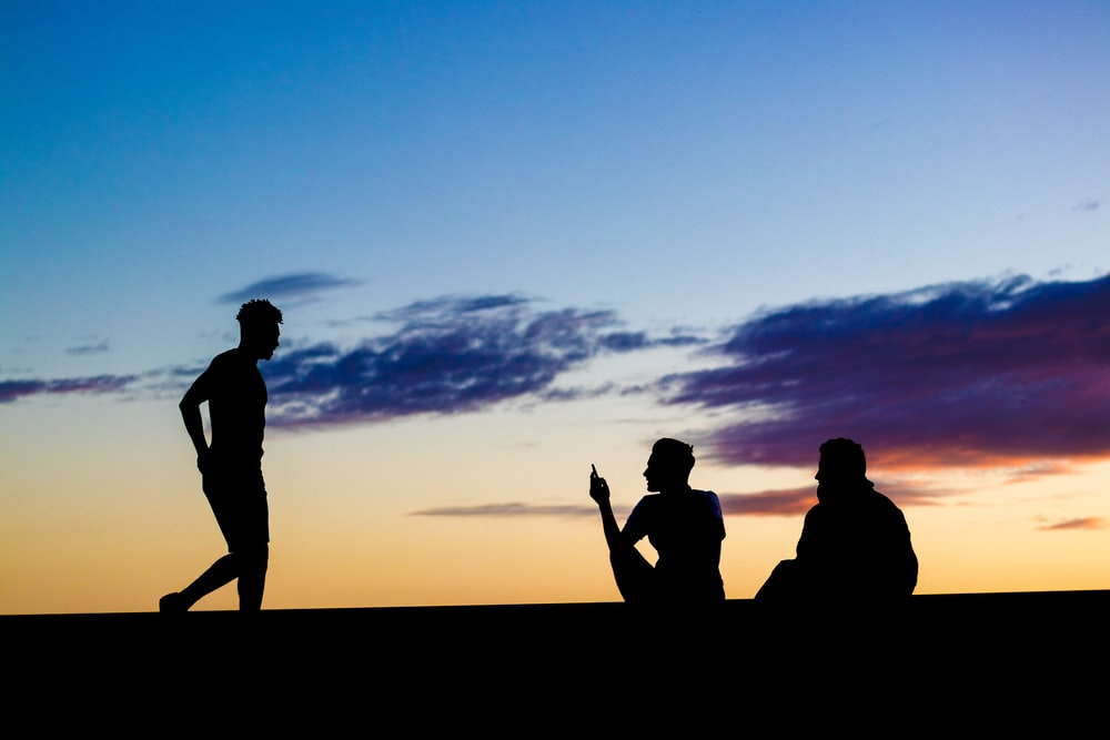 silhouette of three persons under blue and orange skies