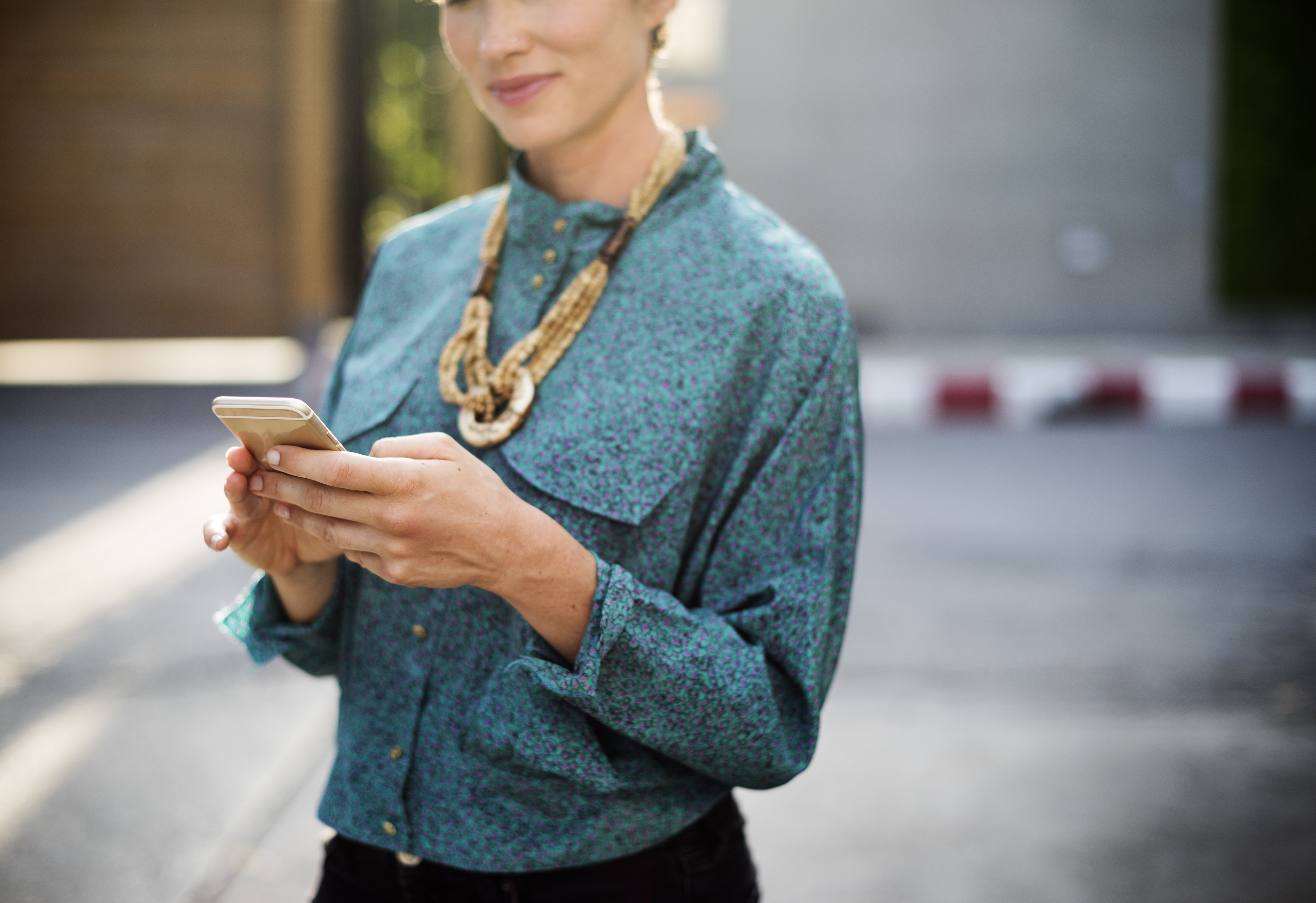woman with brown necklace holding gold smartphone