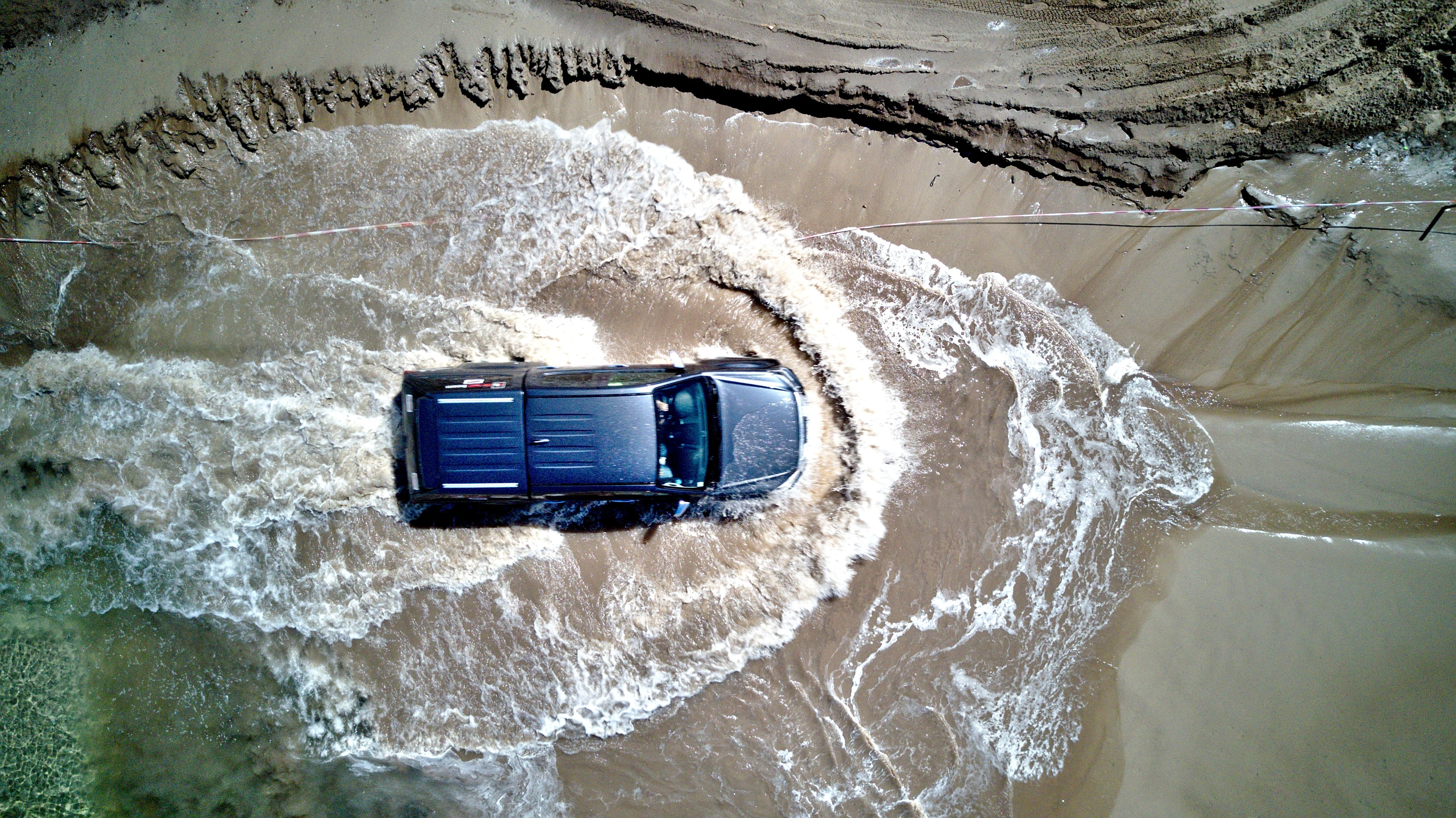 Drone view of the 4x4 SUV driving through the water on the sand beach at Loon op Zand, North Brabant, Netherlands