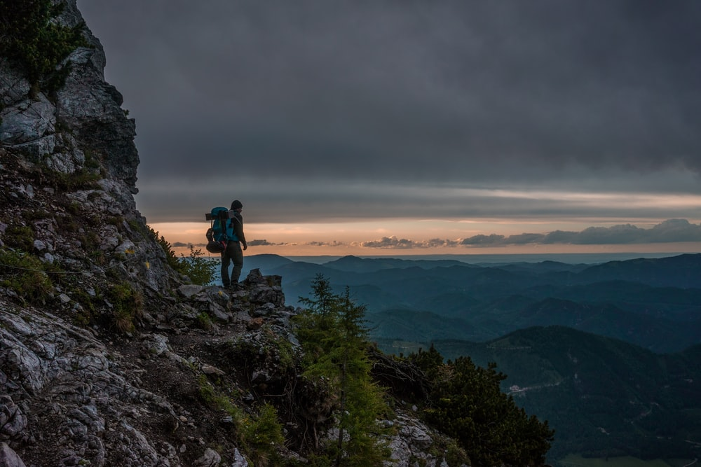 person standing near cliff with view of mountains under nimbus clouds