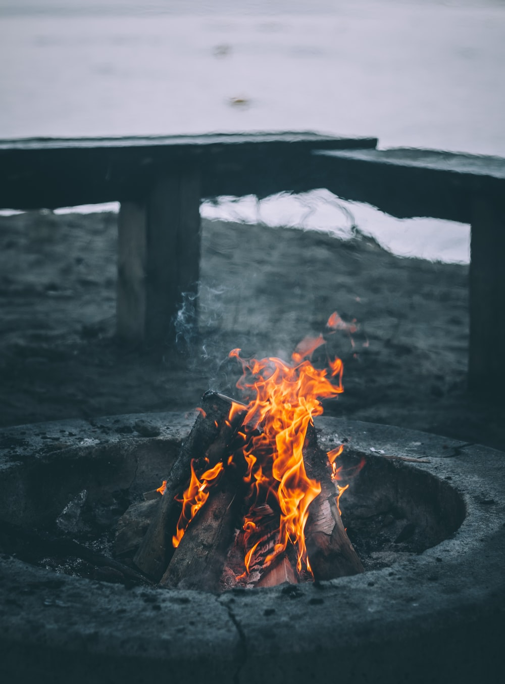 bonfire near bench and sea at daytime
