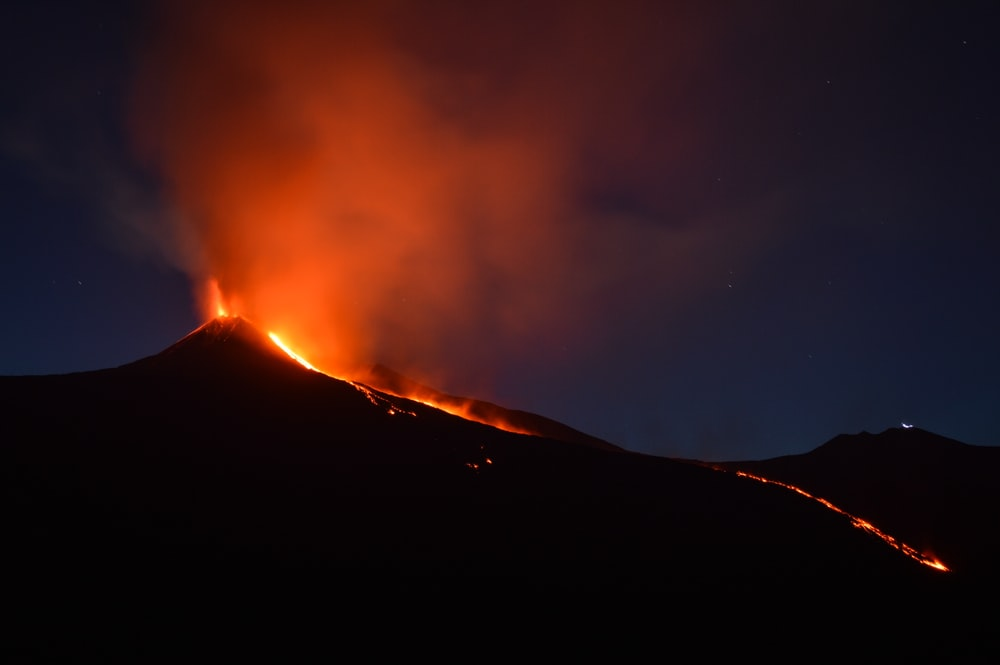 black mountain with flowing lava at nighttime