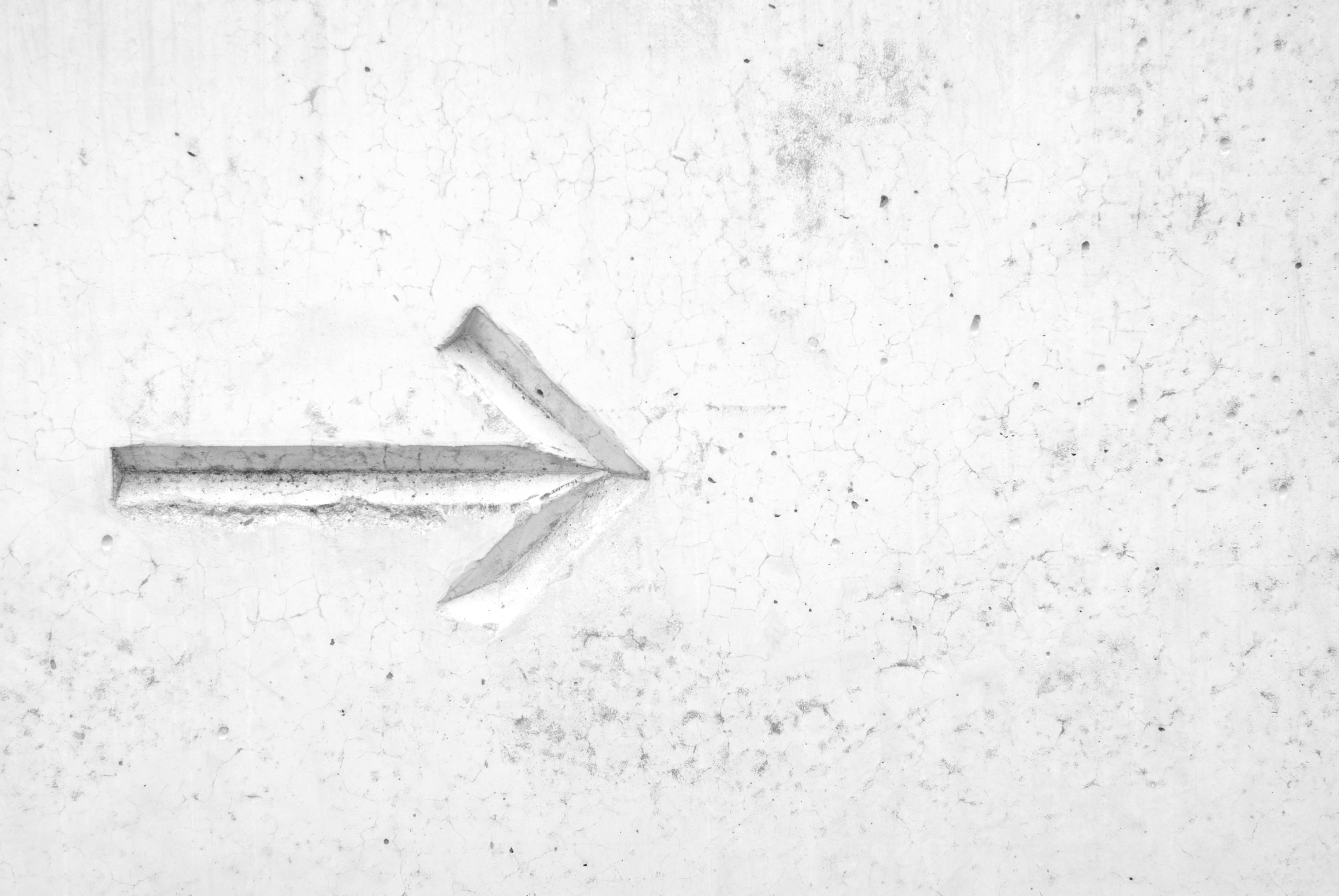 A direction arrow etched in a white wall