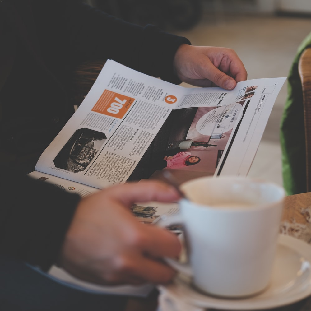 person reading while holding white ceramic mug