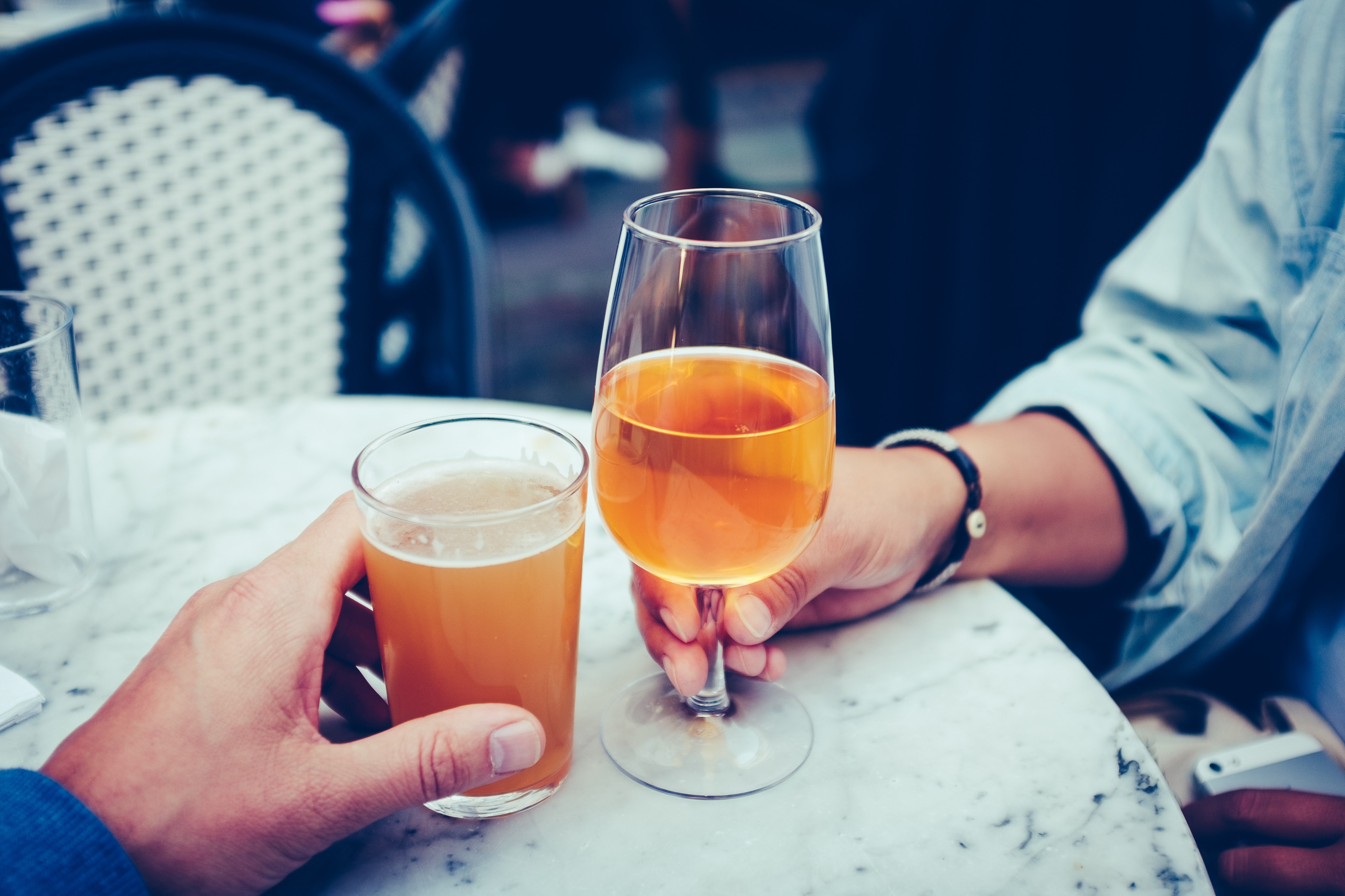 Two people drinking beer and wine at a marble table