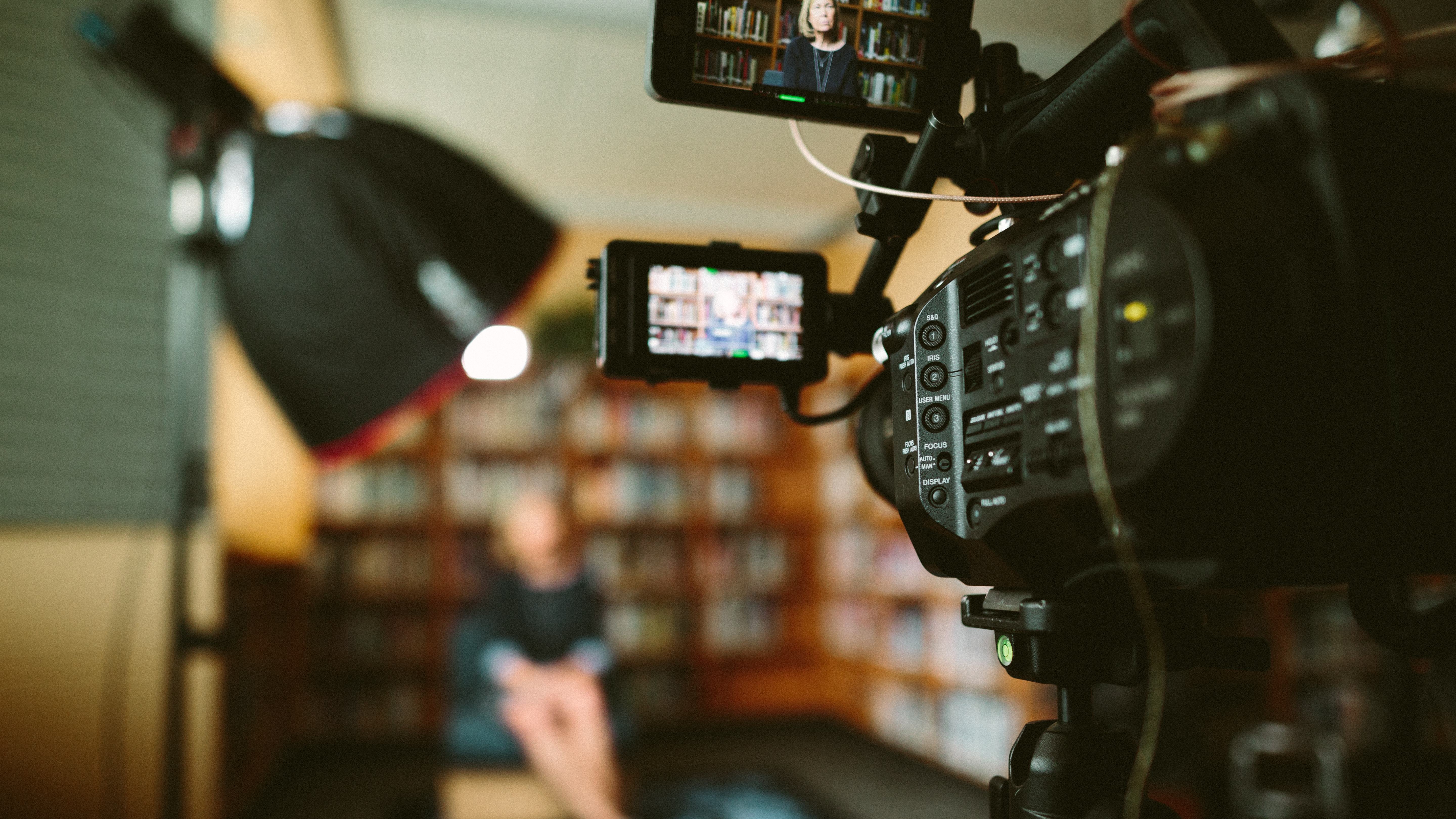 Photo of a black camera recording a person sitting in front of bookshelves in a dimly lit room