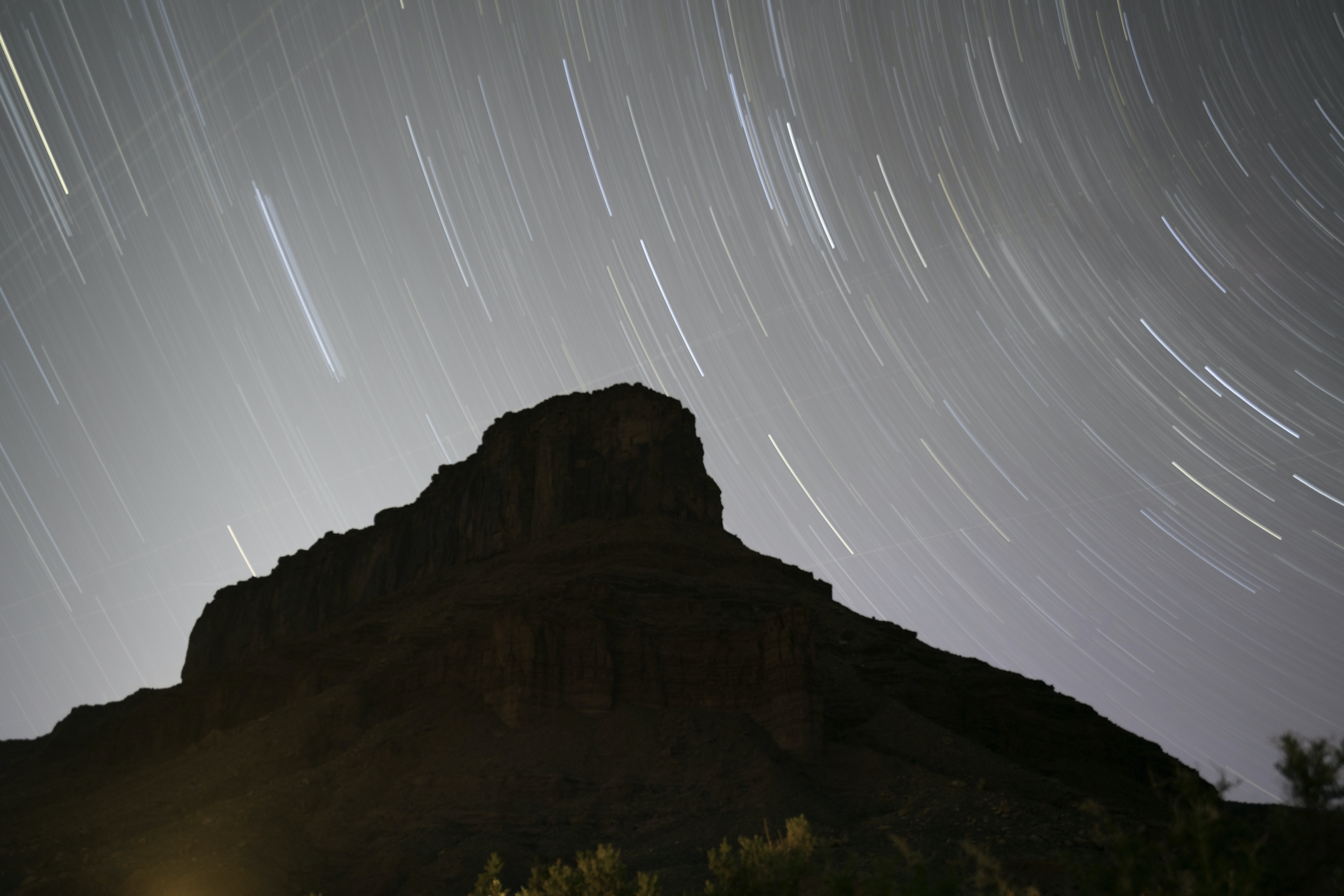 A long exposure shot of stars swirling around a rocky mountain in Moab